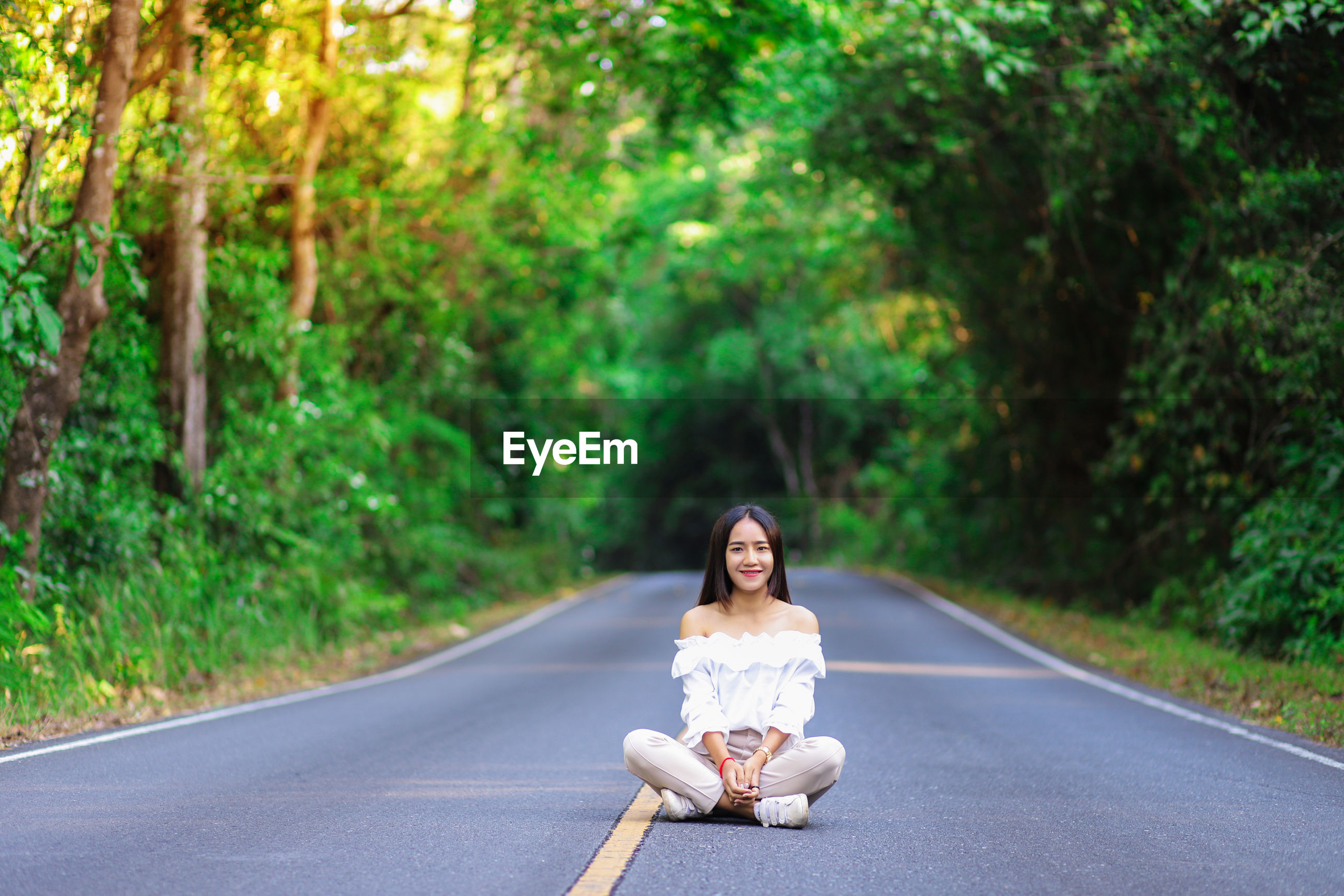 Full length portrait of smiling young woman sitting on country road in forest