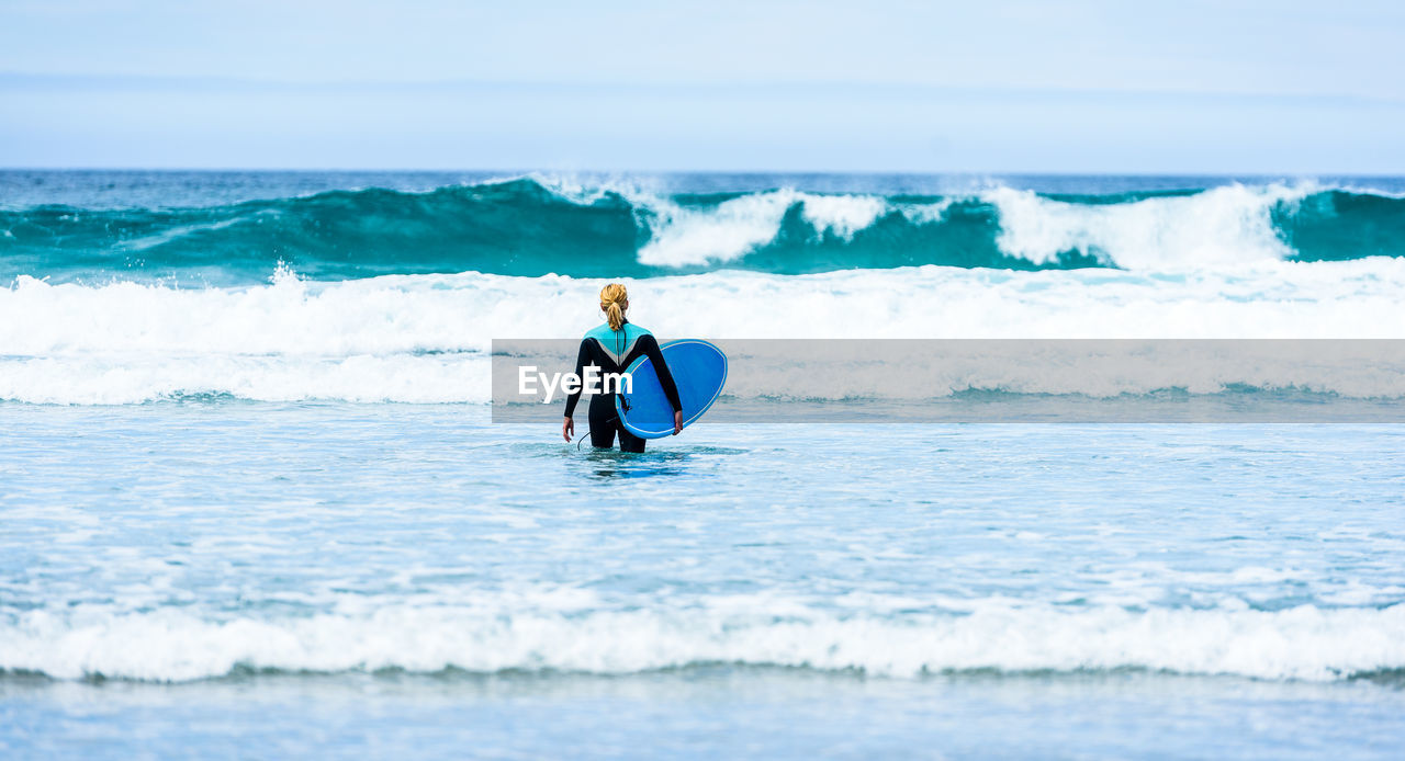 Woman With Surfboard Wading In Sea Against Sky