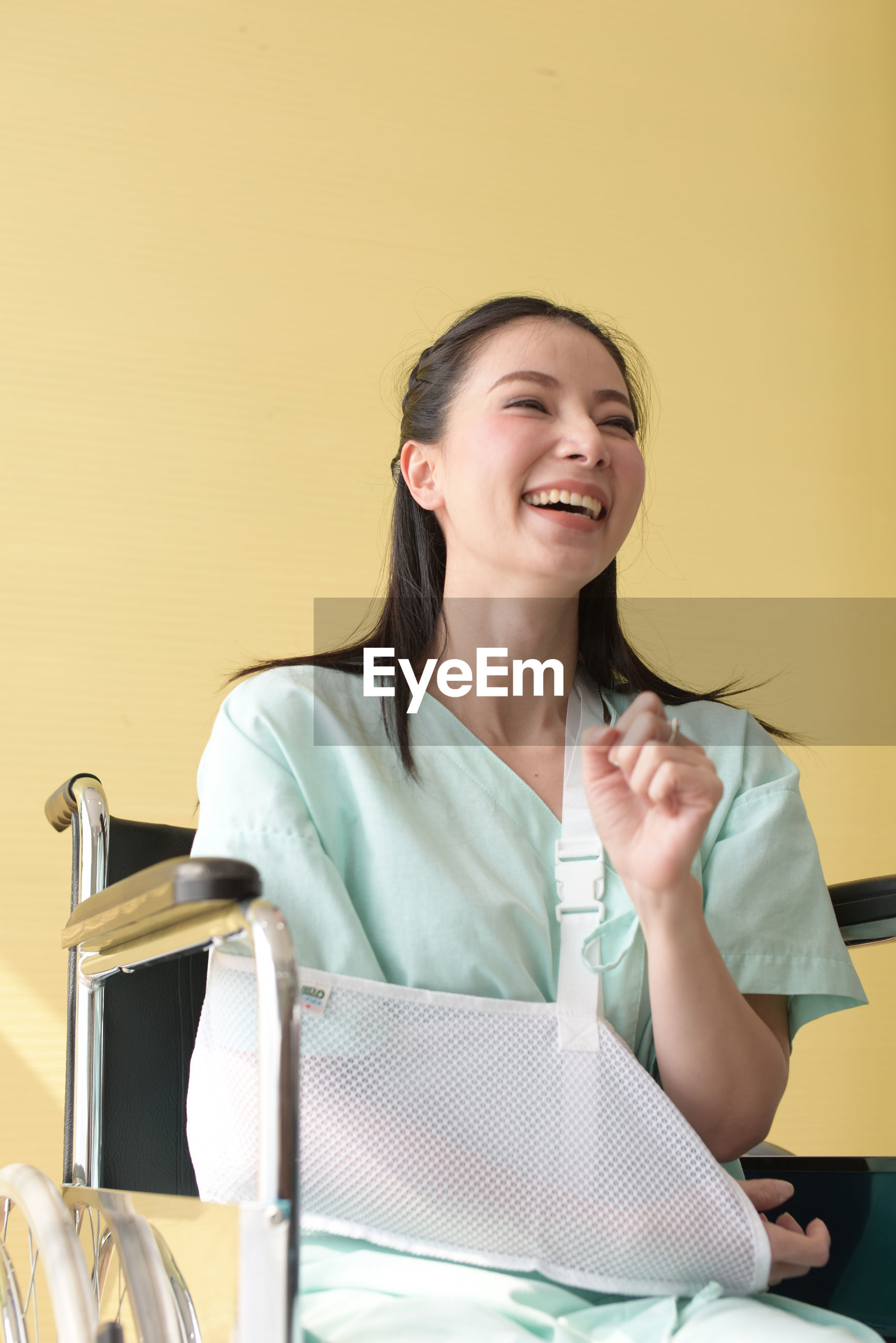 Smiling disabled woman sitting on wheelchair against wall