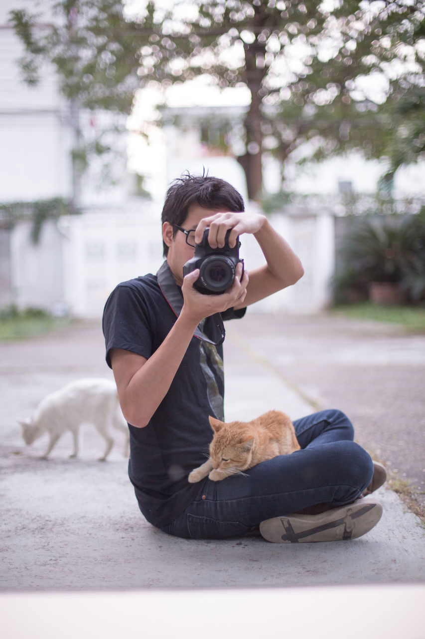 Man Photographing While Ginger Cat Lying On Lap