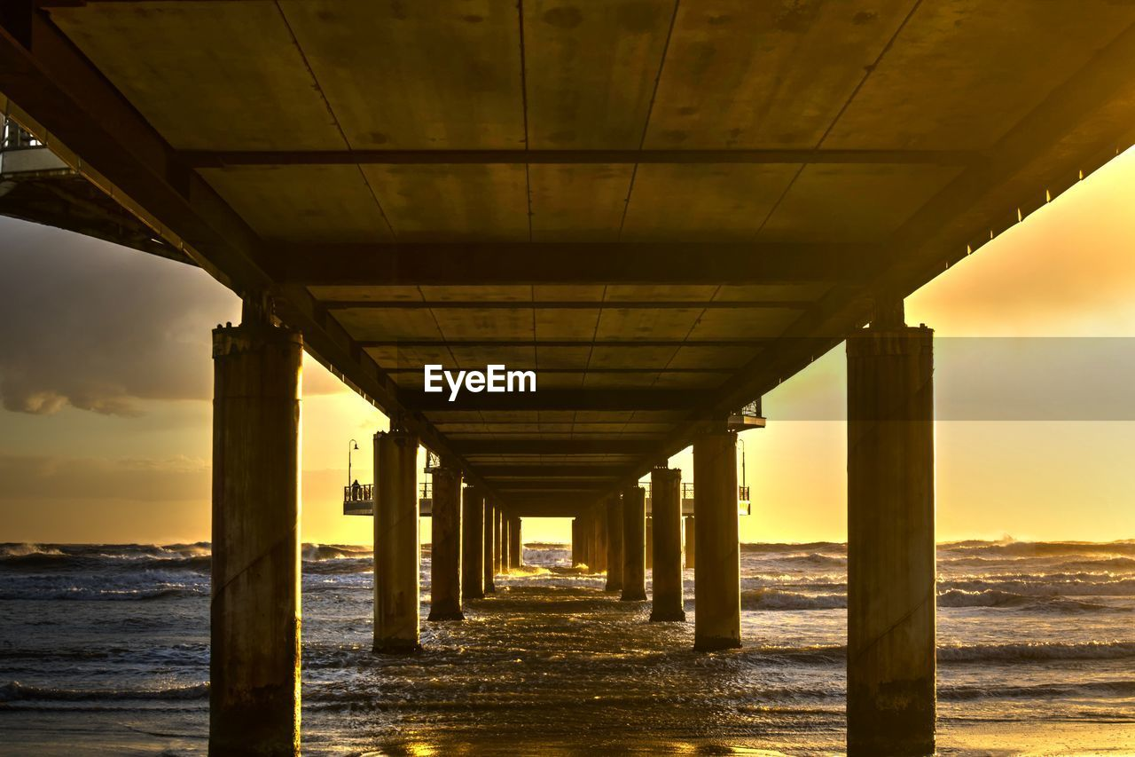 architectural column, architecture, built structure, water, sea, bridge, pier, connection, sky, bridge - man made structure, no people, nature, underneath, in a row, sunset, below, beach, diminishing perspective, the way forward, outdoors, horizon over water, long, ceiling
