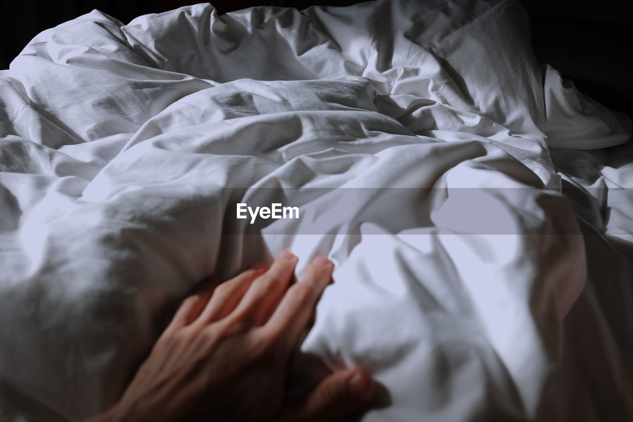 Cropped Hand Touching Blanket On Bed At Home