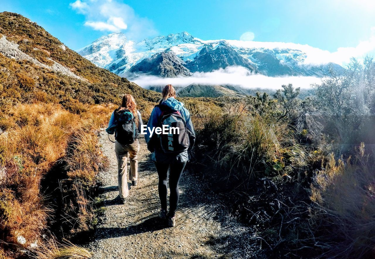 mountain, hiking, walking, rear view, adventure, backpack, nature, full length, real people, hiker, leisure activity, mountain range, togetherness, day, beauty in nature, sky, landscape, lifestyles, grass, cold temperature, outdoors, men, two people, healthy lifestyle, scenics, winter, friendship, women, adult, people