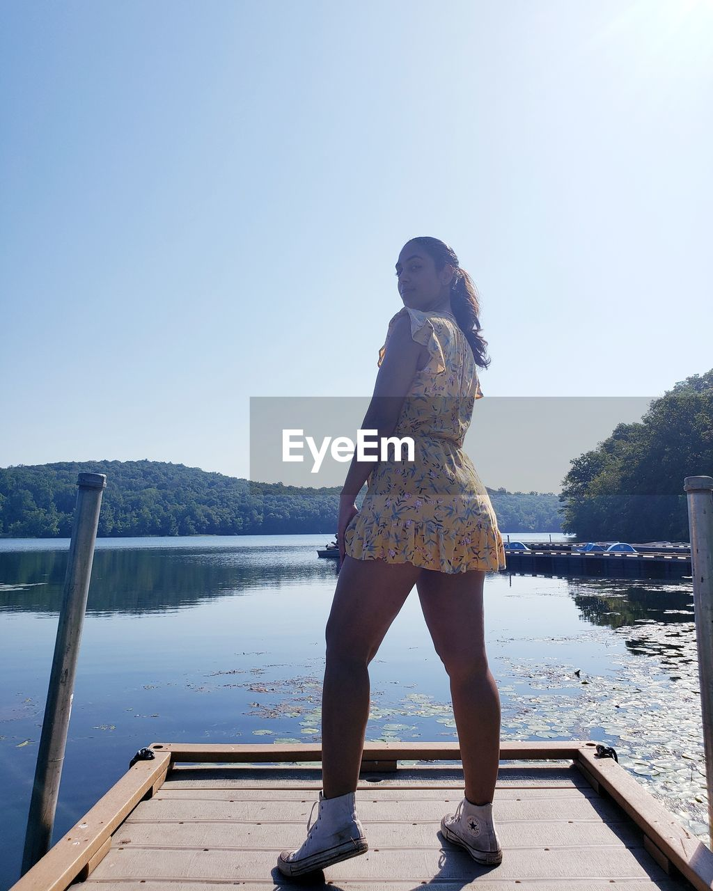 REAR VIEW OF WOMAN LOOKING AT PIER ON LAKE