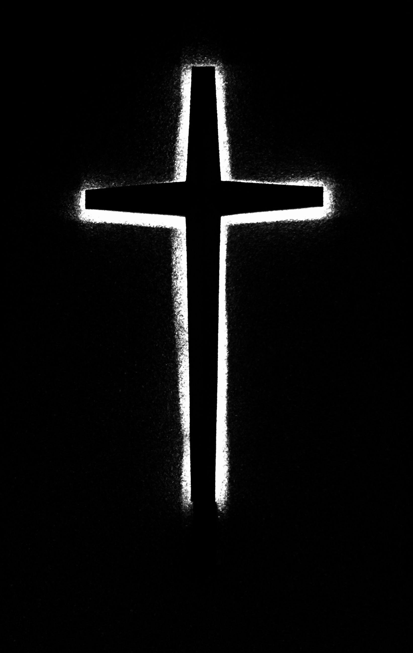 Cross against black background