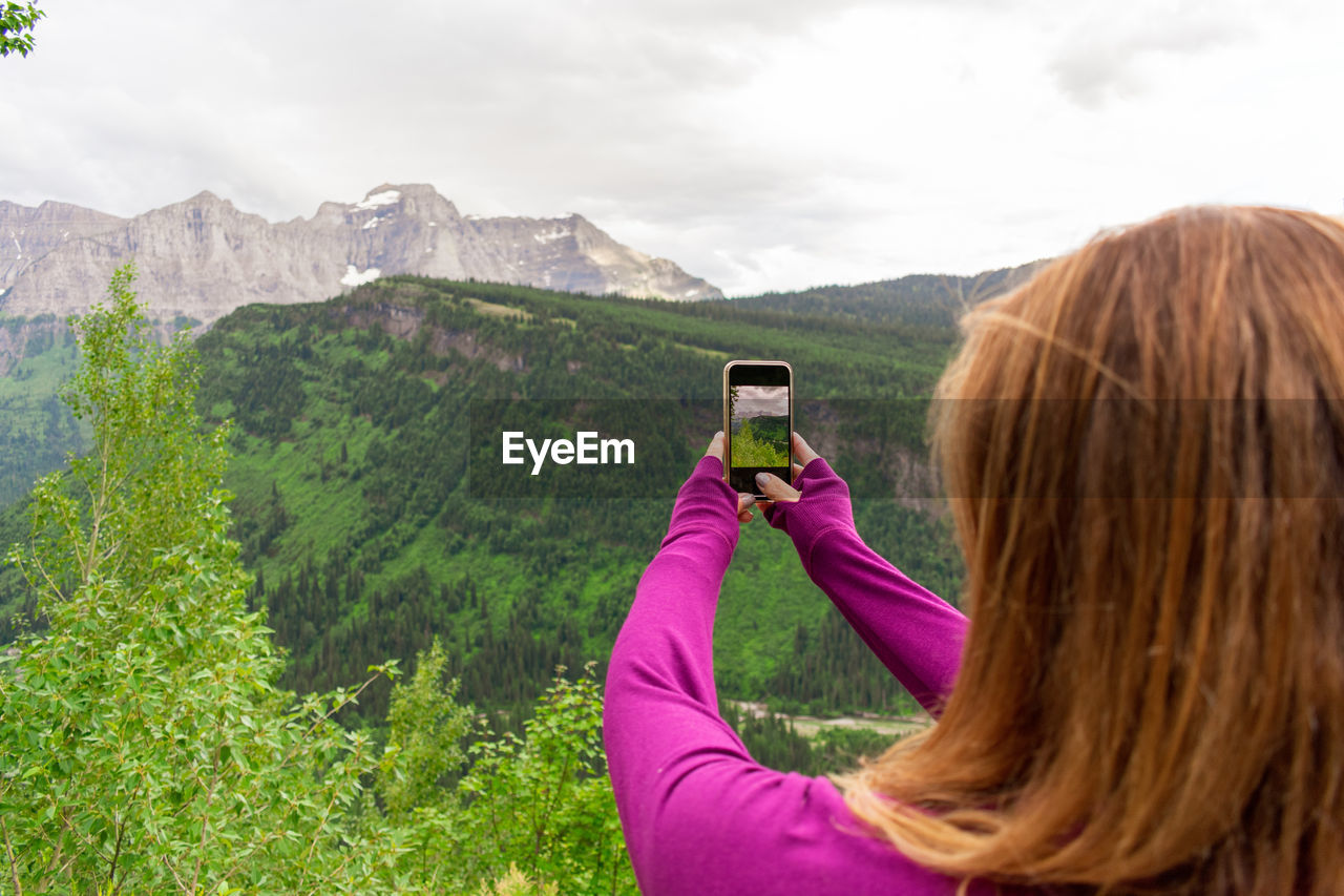 Rear view of woman photographing against mountain