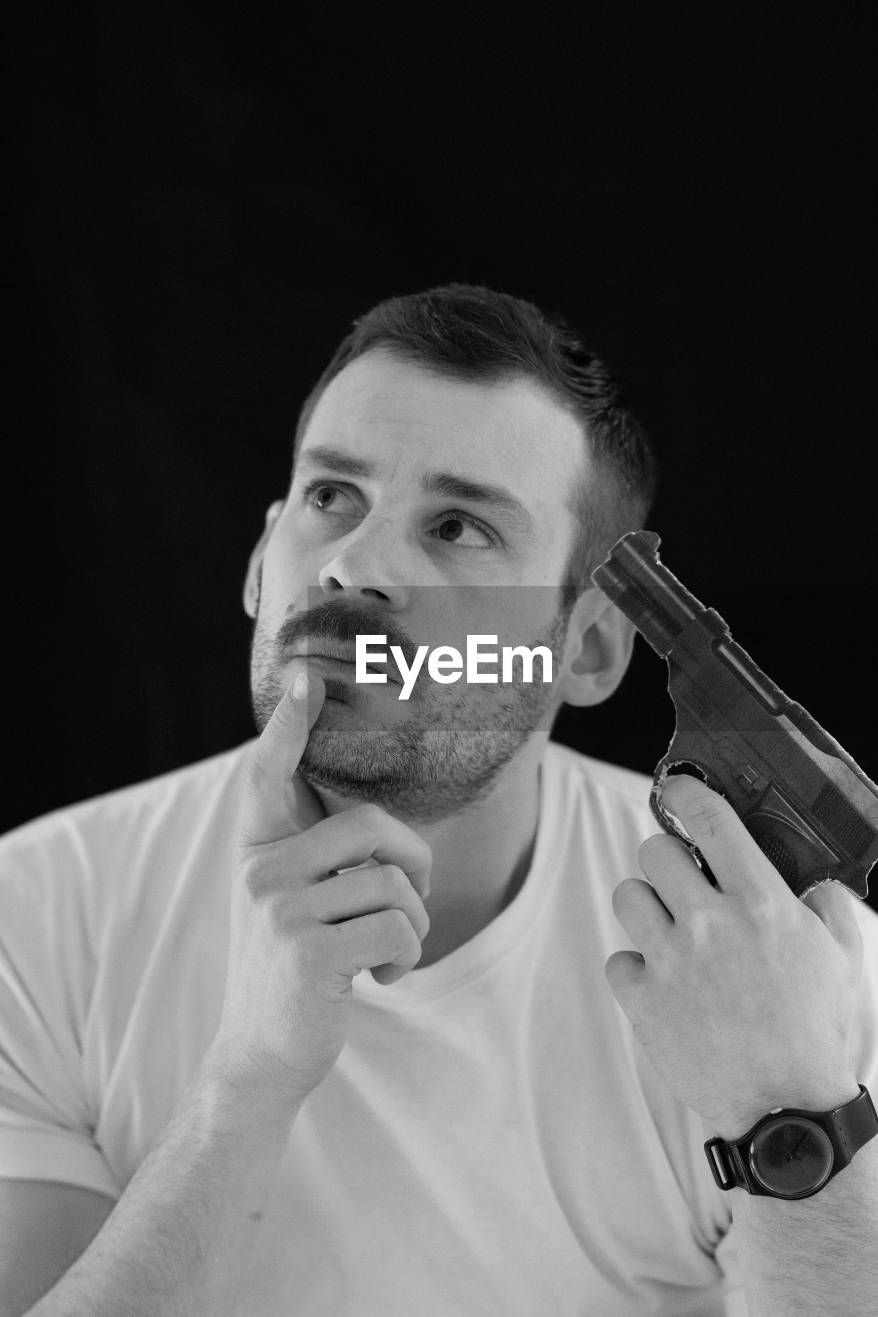 Thoughtful man attempting suicide with gun against black background