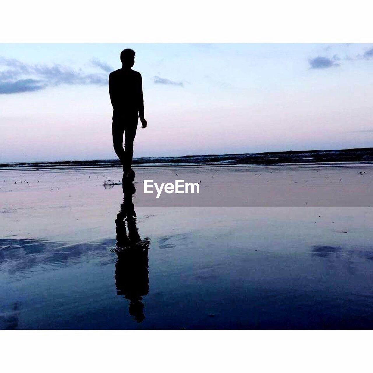 silhouette, water, reflection, beach, sea, full length, one person, standing, real people, sky, walking, men, horizon over water, outdoors, leisure activity, beauty in nature, tranquility, nature, scenics, sunset, lifestyles, day, people