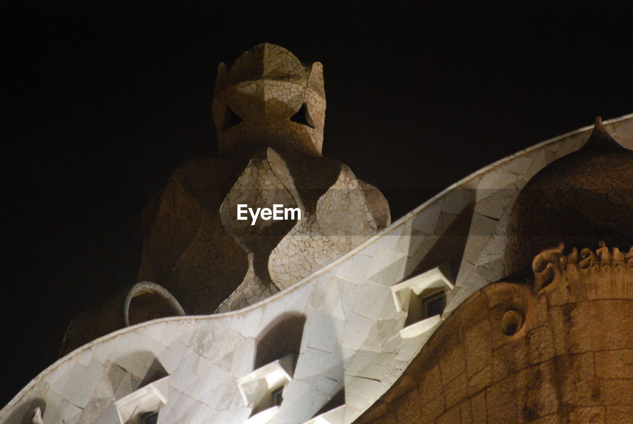 low angle view, no people, night, sculpture, outdoors, clear sky, black background