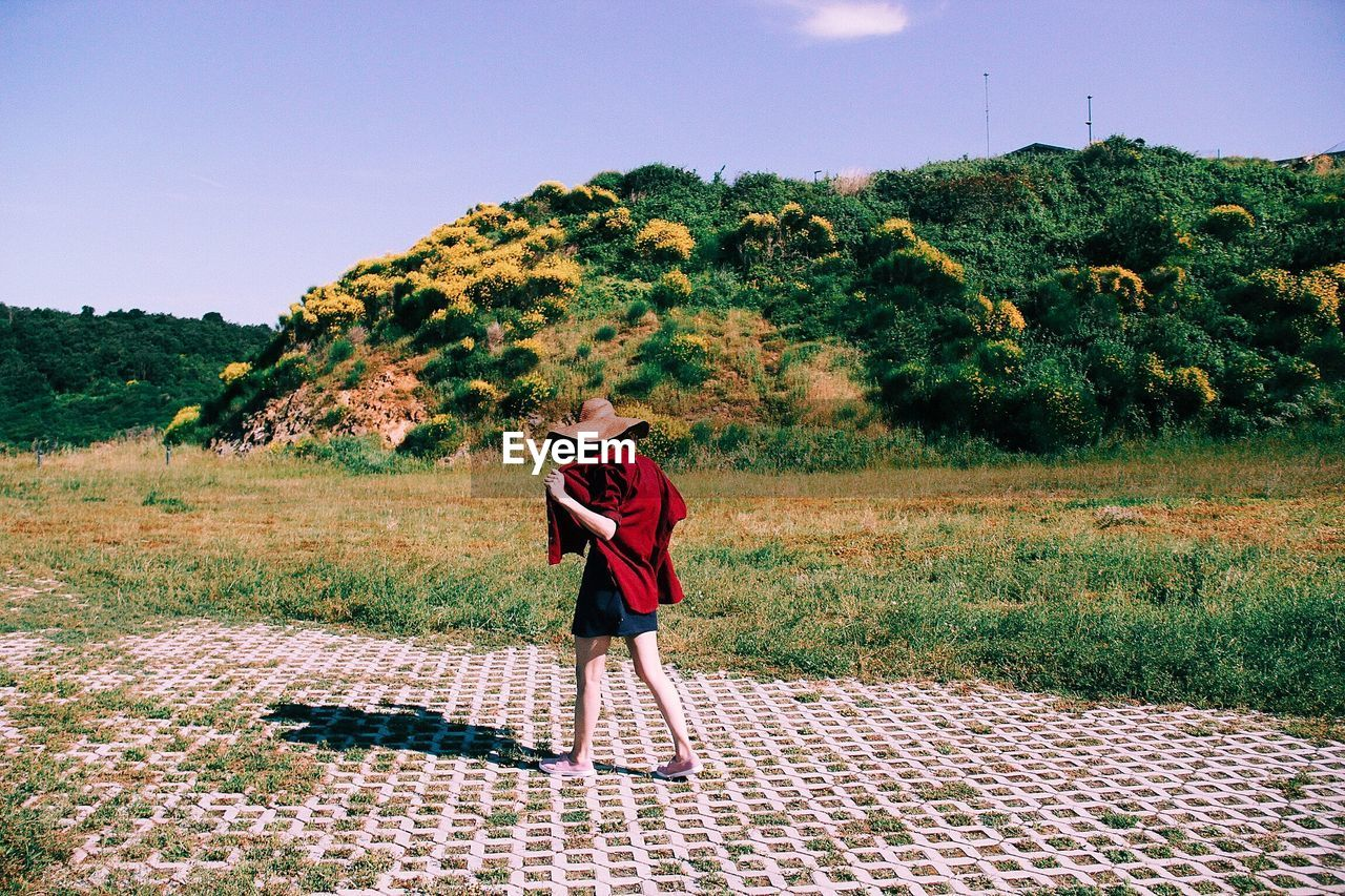 Full Length Of Woman Walking Against Sky During Sunny Day