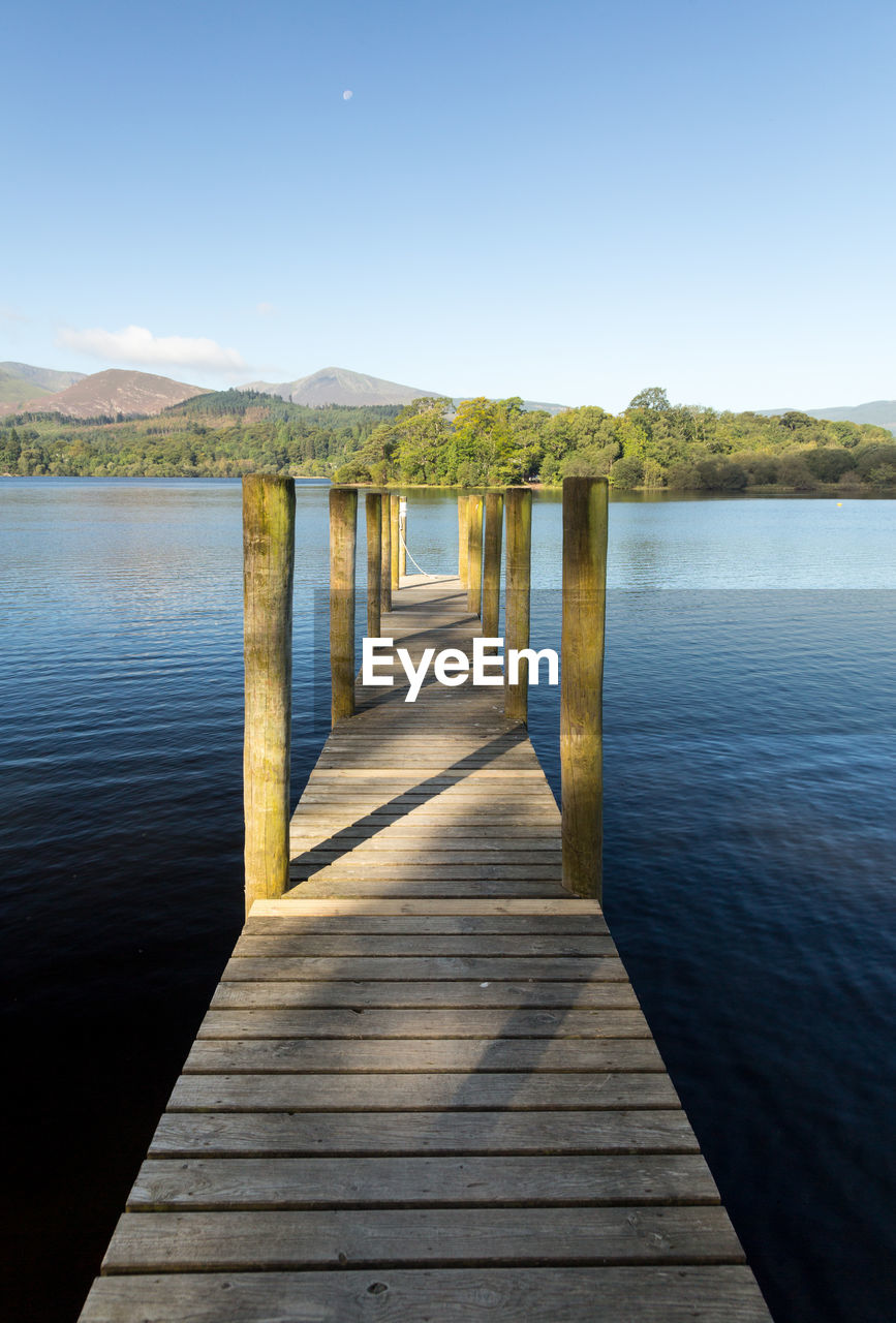water, sky, tranquility, the way forward, tranquil scene, wood - material, direction, pier, beauty in nature, nature, no people, scenics - nature, lake, day, clear sky, idyllic, reflection, mountain, outdoors, diminishing perspective, wood, long, wood paneling, wooden post
