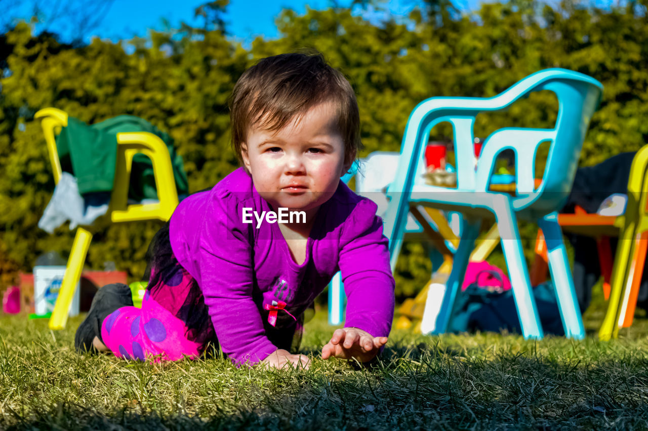 Portrait Of Baby Girl Crawling In Back Yard During Sunny Day