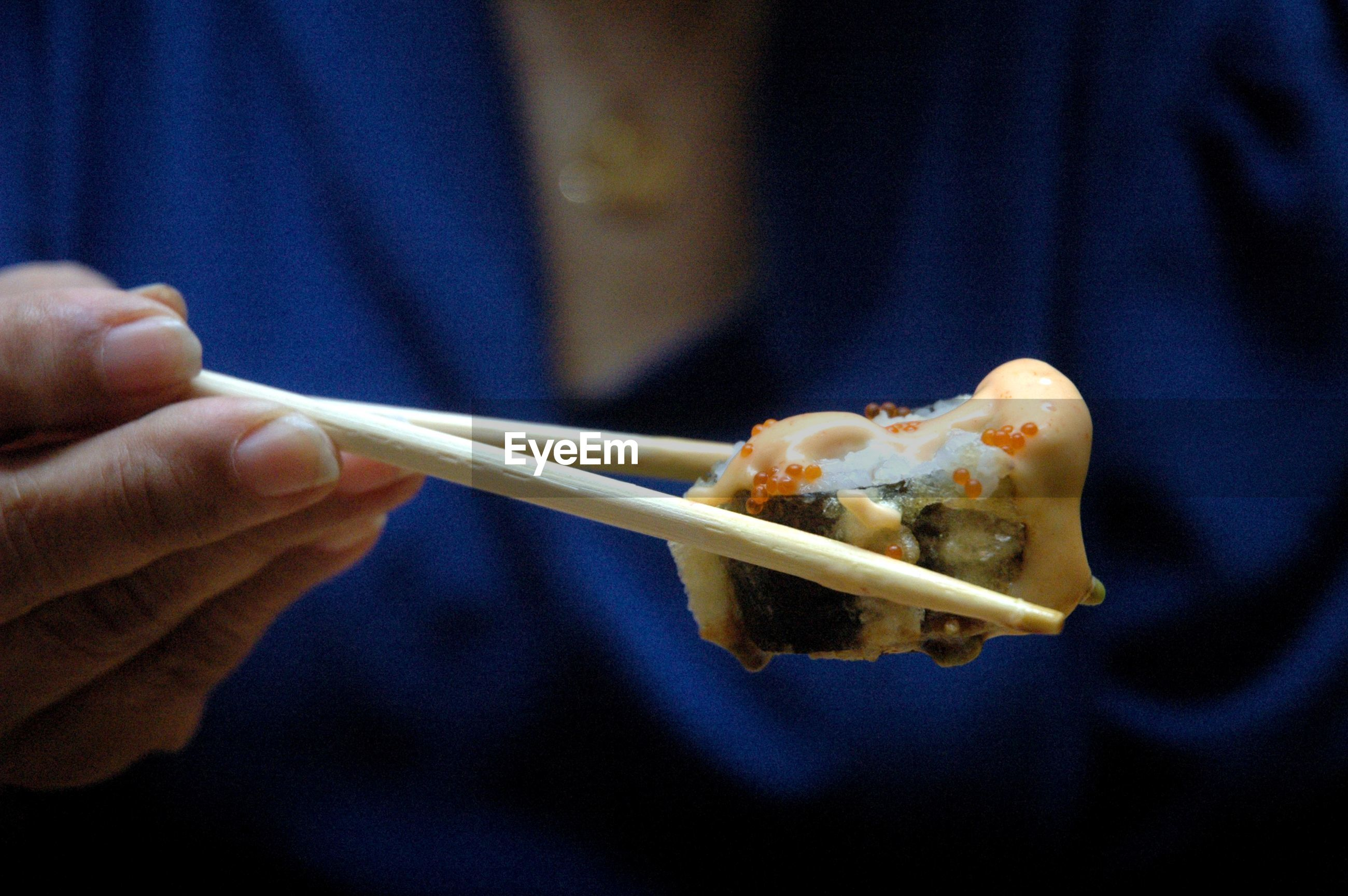 Midsection of woman holding sushi with chopsticks
