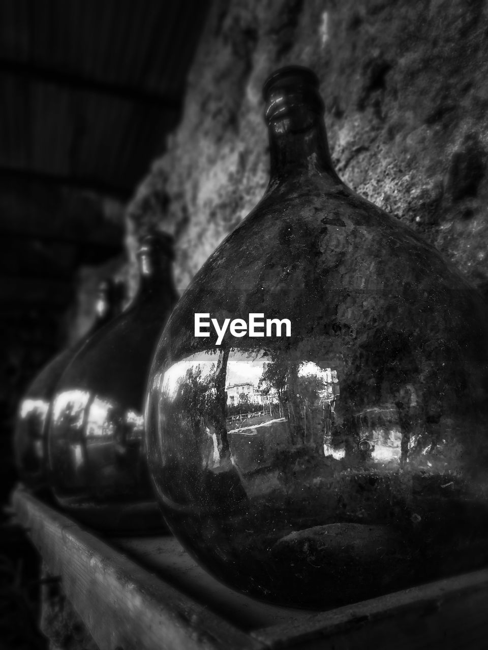 bottle, indoors, container, no people, still life, close-up, old, focus on foreground, glass - material, drink, transparent, wall - building feature, single object, alcohol, wine bottle, food and drink, wine, metal, refreshment, architecture
