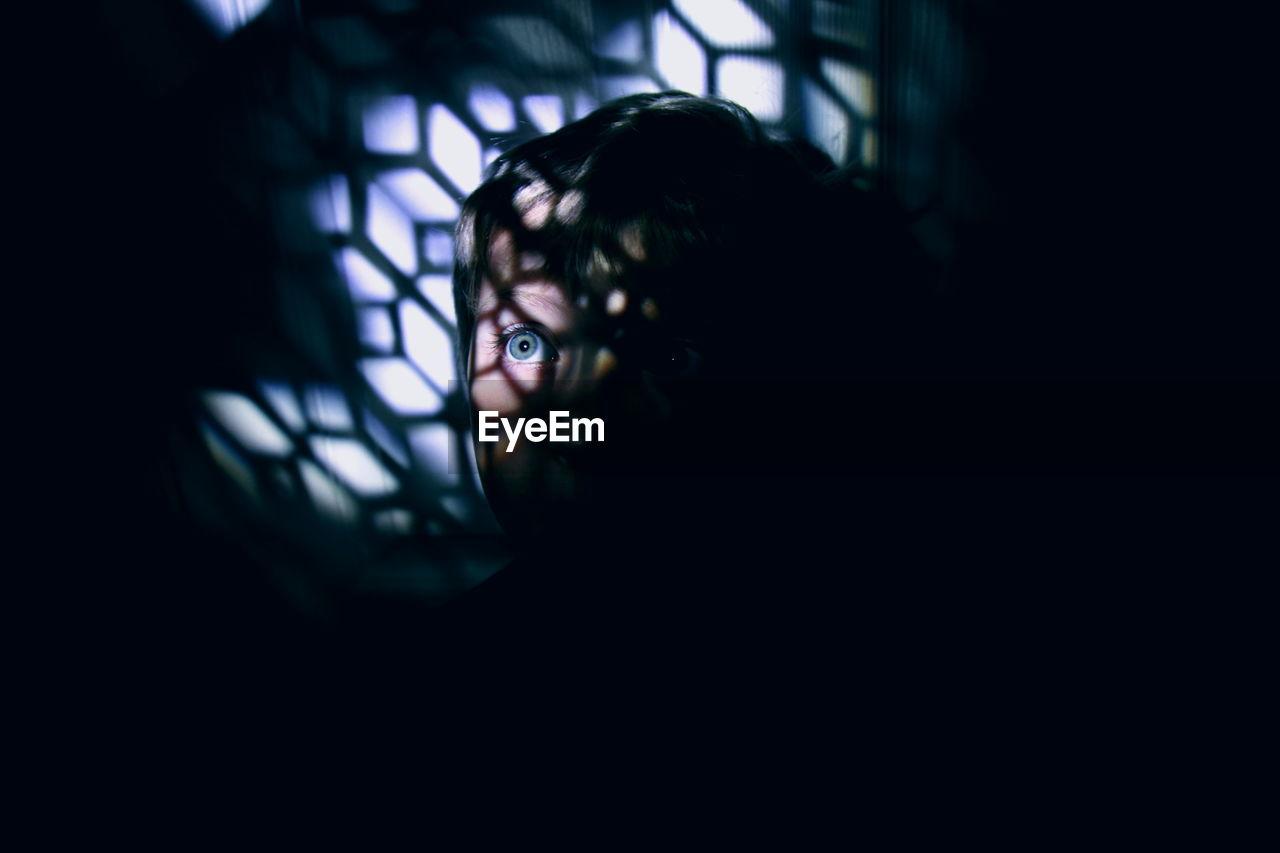 View Of Boy Hiding In Dark Room