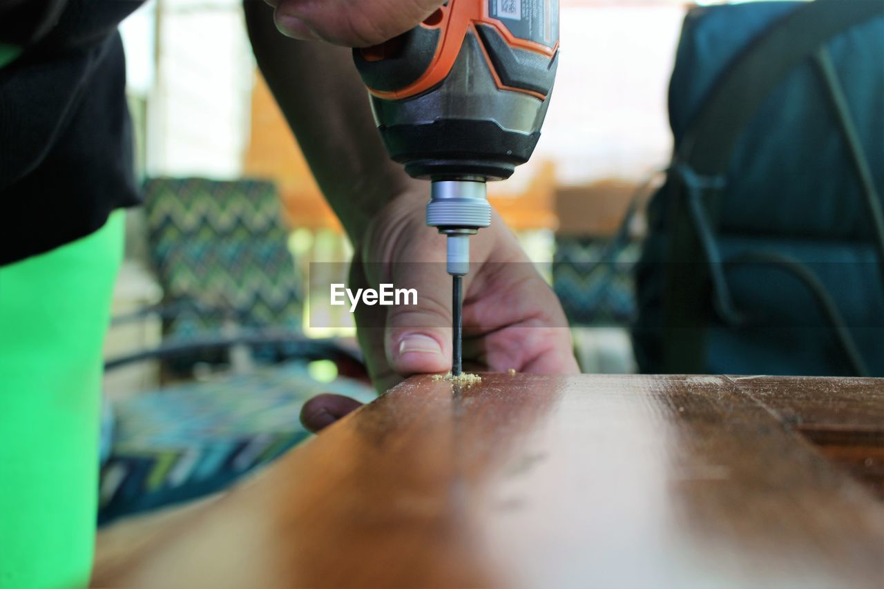 Midsection of carpenter drilling wood
