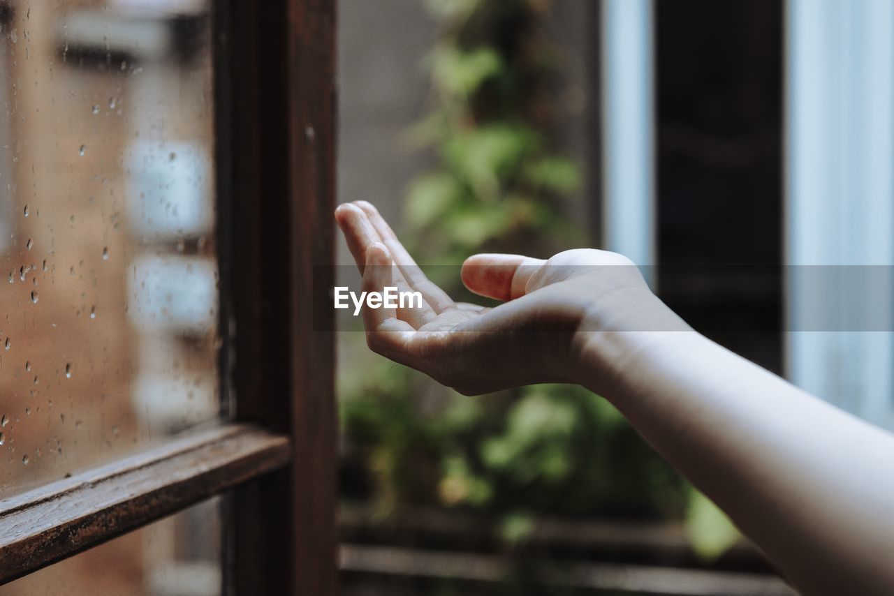 Cropped Hand Of Person At Window During Rainy Season