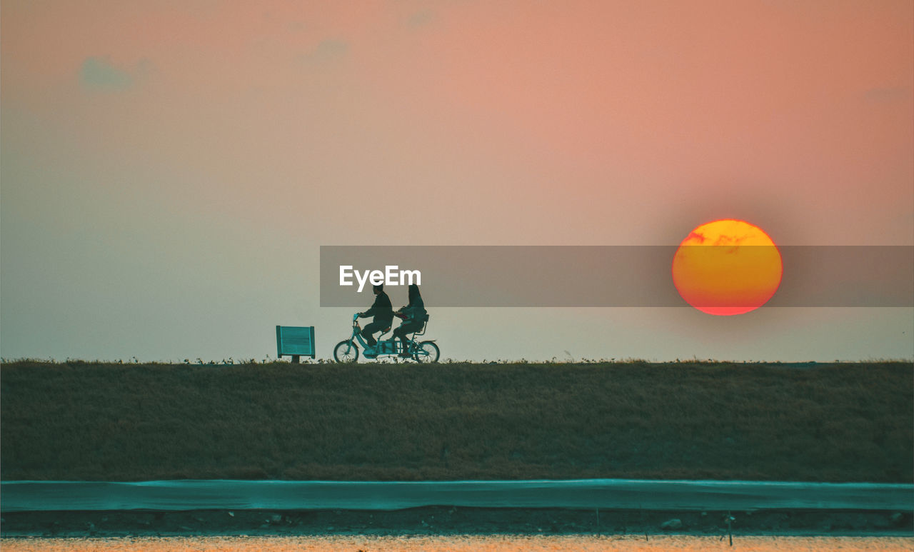 sky, sunset, transportation, nature, mode of transportation, orange color, men, water, land vehicle, land, beauty in nature, field, real people, plant, leisure activity, scenics - nature, outdoors, riding, people