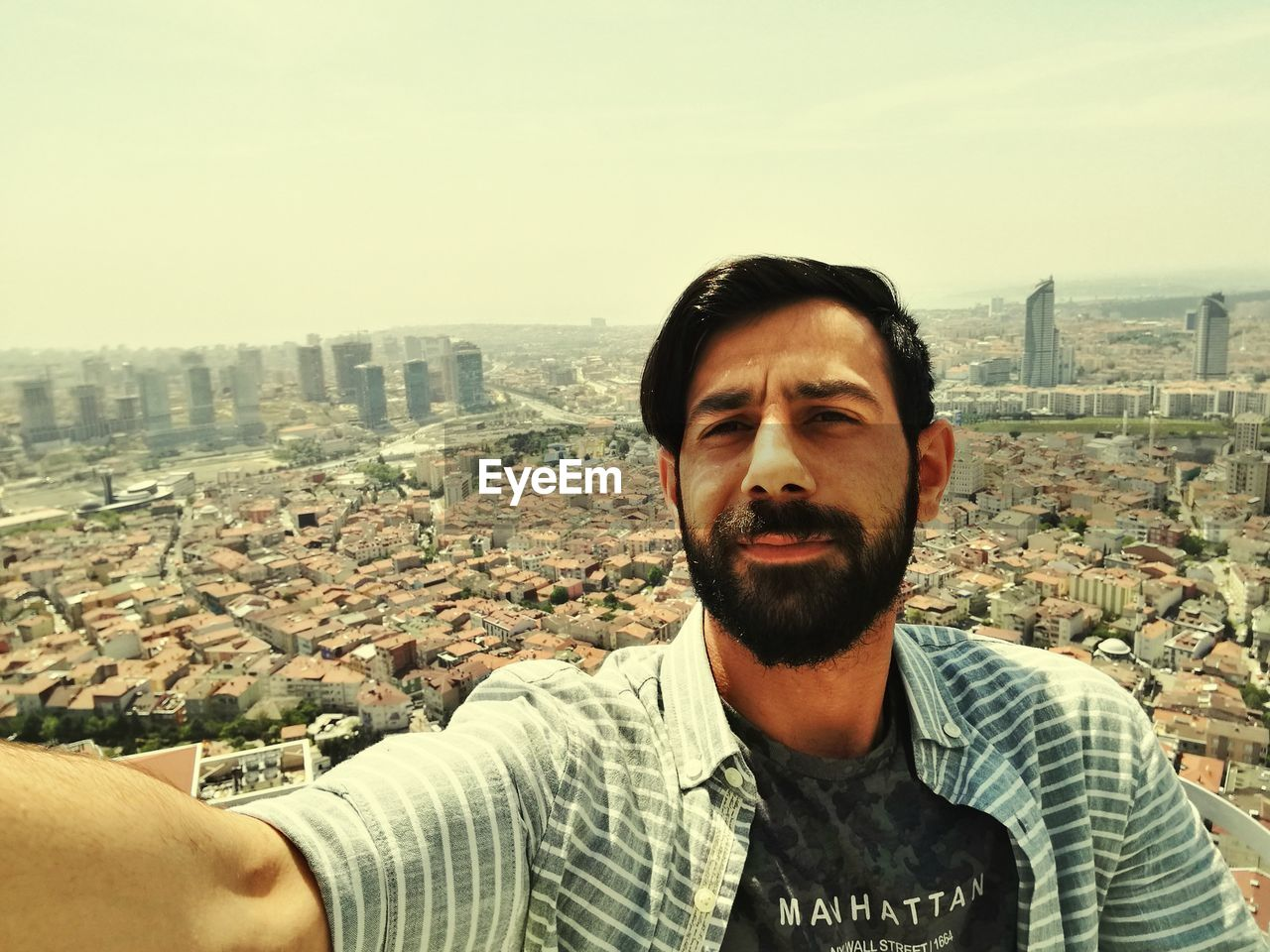 Portrait Of Young Bearded Man Against Cityscape