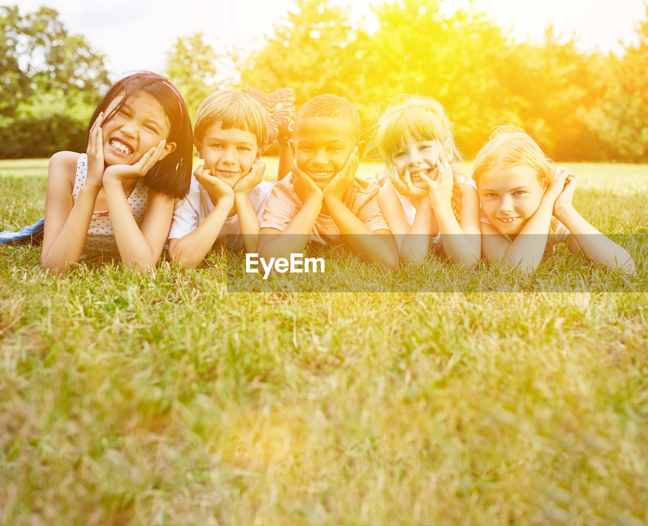 Portrait Of Smiling Friends Lying On Field At Park