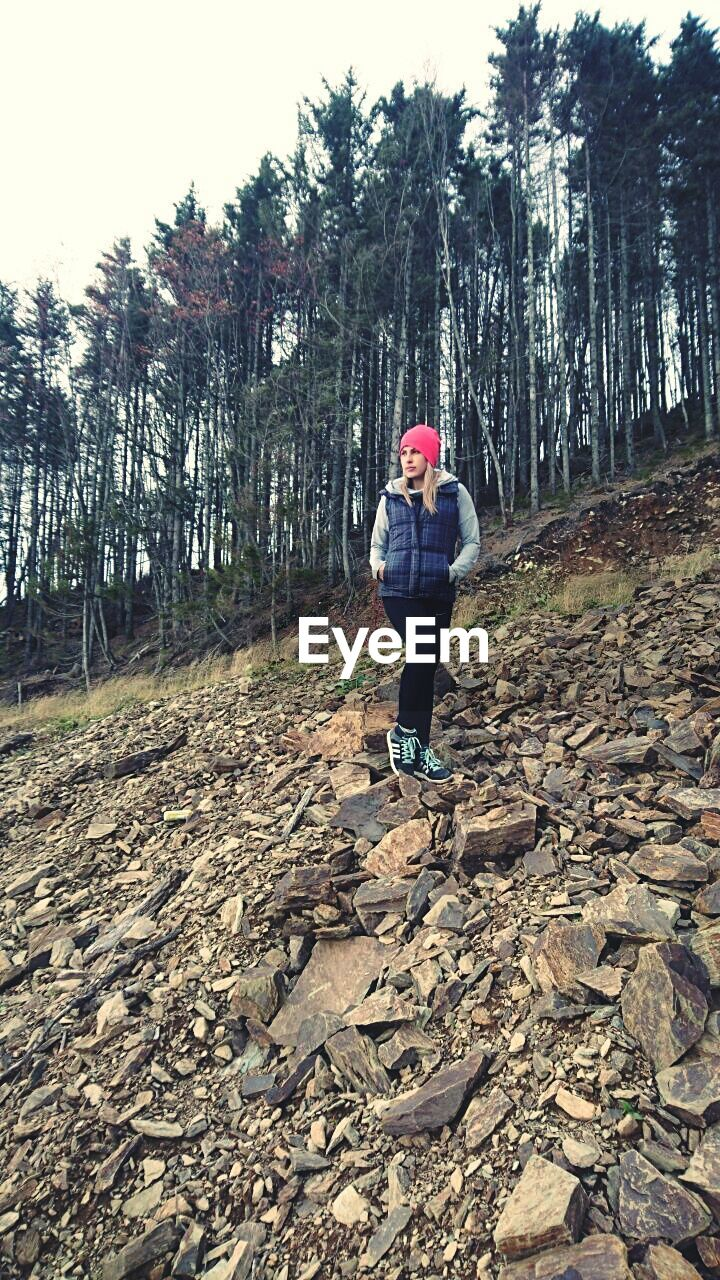 full length, one person, real people, tree, lifestyles, leisure activity, women, outdoors, rear view, day, young women, adventure, forest, young adult, nature, standing, headwear, one woman only, sky, adult, adults only, people