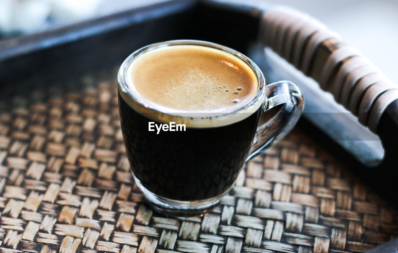 Close-up of coffee on wicker table