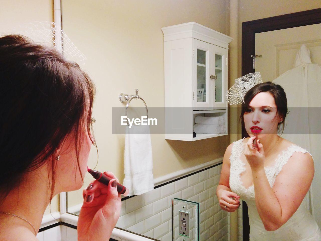 View Of Bride Applying Lipstick In Bathroom