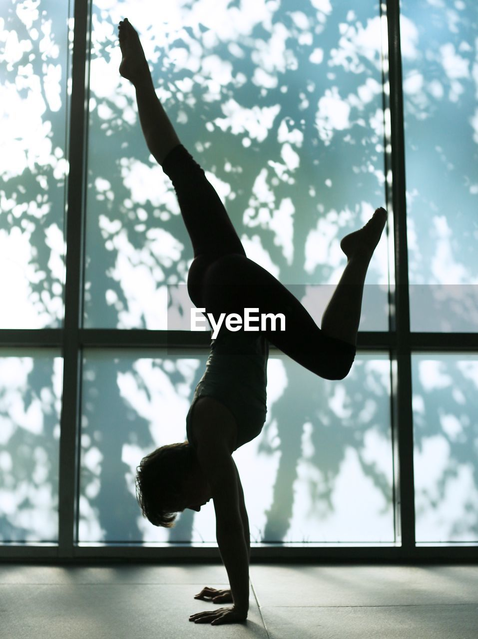 one person, real people, lifestyles, full length, window, sport, balance, flexibility, indoors, vitality, strength, healthy lifestyle, exercising, skill, silhouette, day, leisure activity, nature, practicing, handstand, arms raised
