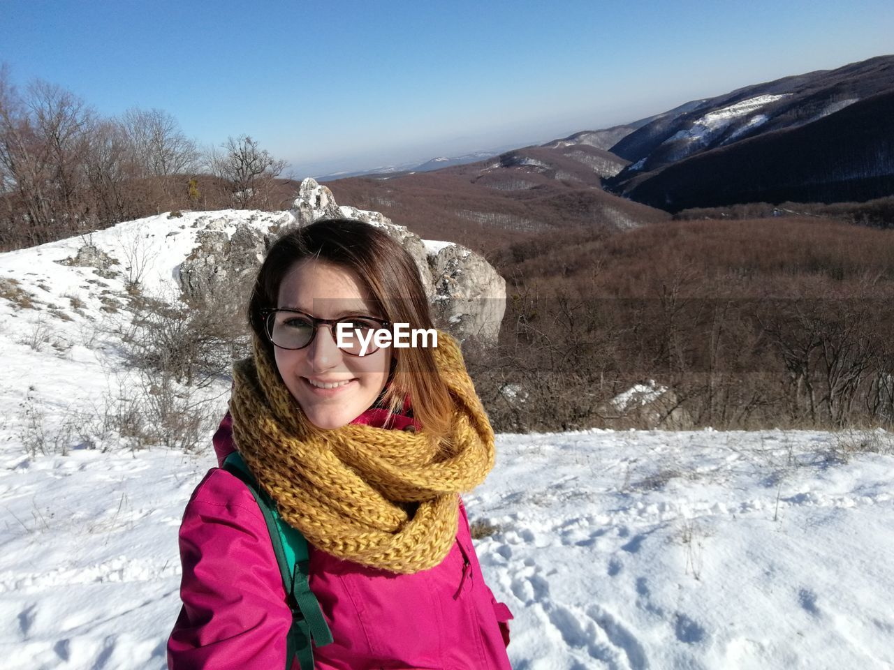 Portrait of smiling young woman standing on snow covered landscape