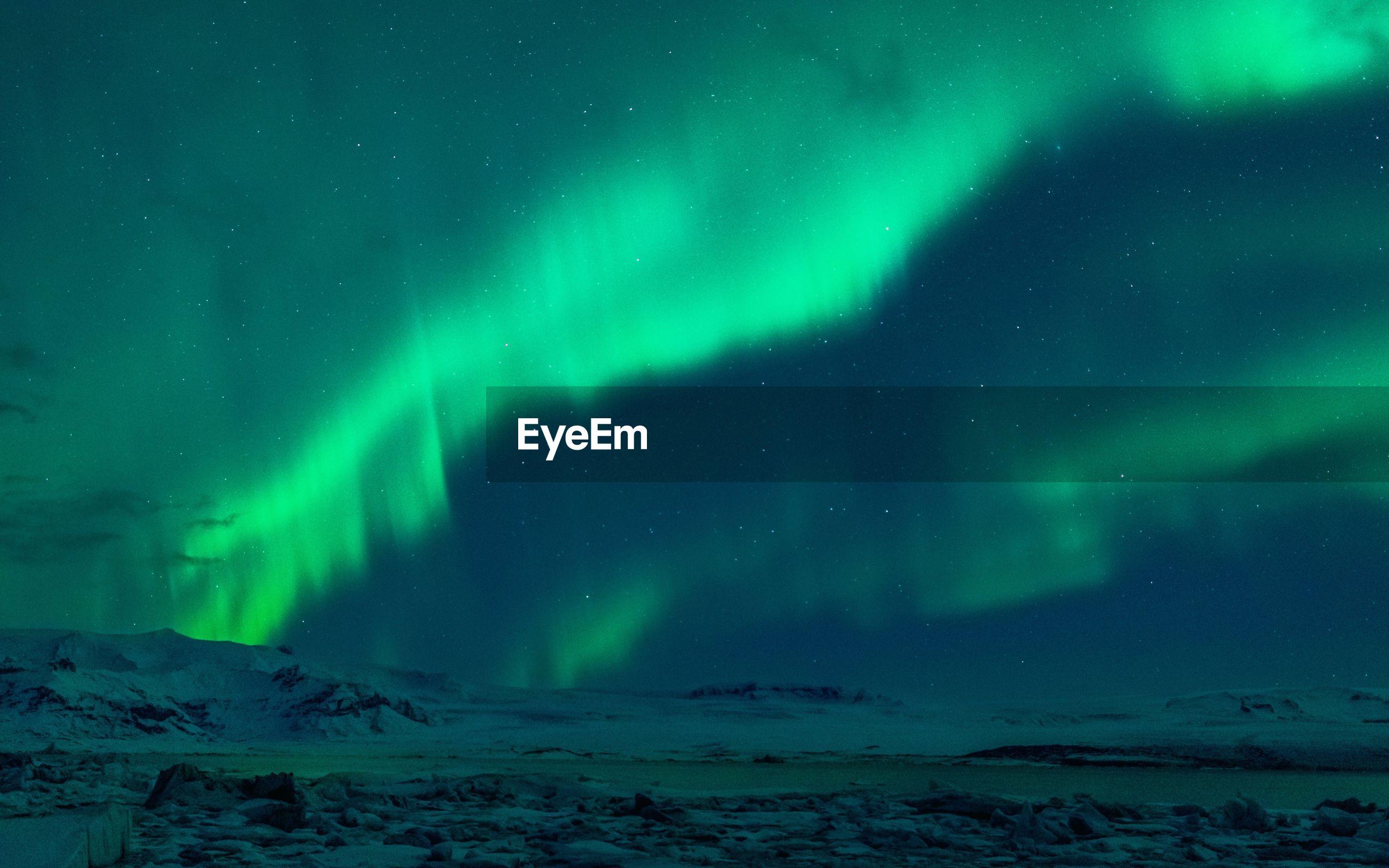 Aurora polaris over frozen landscape against sky