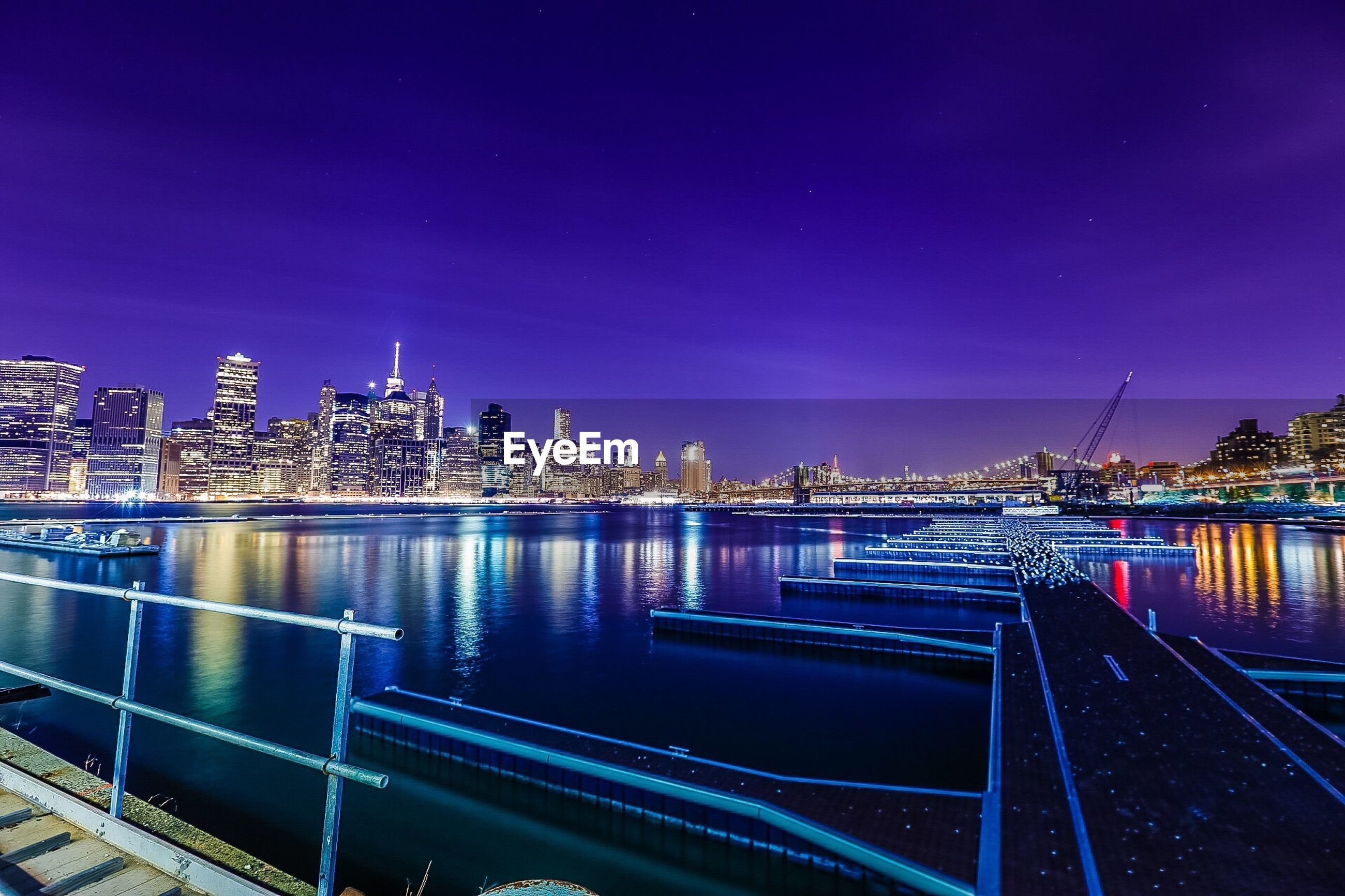 illuminated, night, architecture, building exterior, built structure, city, water, cityscape, river, blue, clear sky, railing, copy space, reflection, sky, modern, skyscraper, city life, lighting equipment, outdoors
