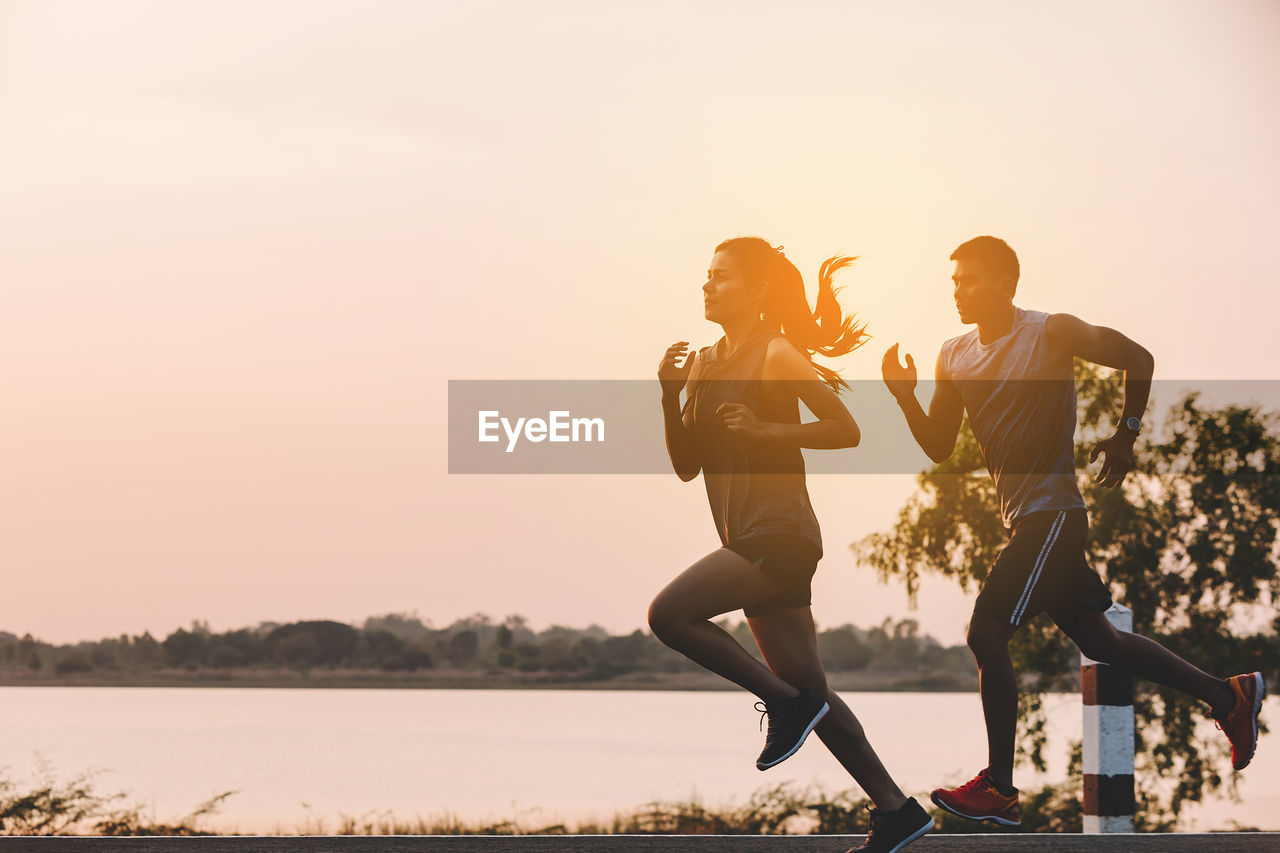 sky, sunset, real people, two people, togetherness, friendship, lifestyles, nature, leisure activity, copy space, men, water, women, sport, bonding, people, young adult, clear sky, full length, couple - relationship, outdoors