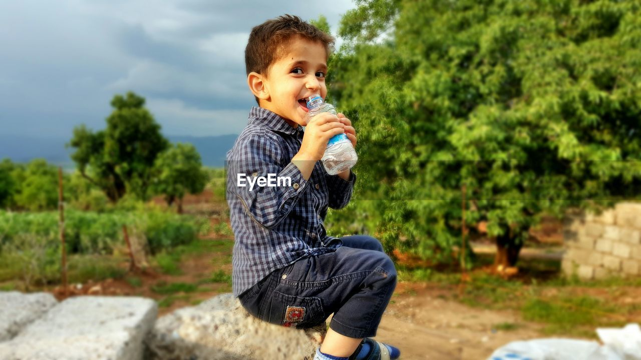 Portrait of smiling boy drinking water from bottle while sitting on rock