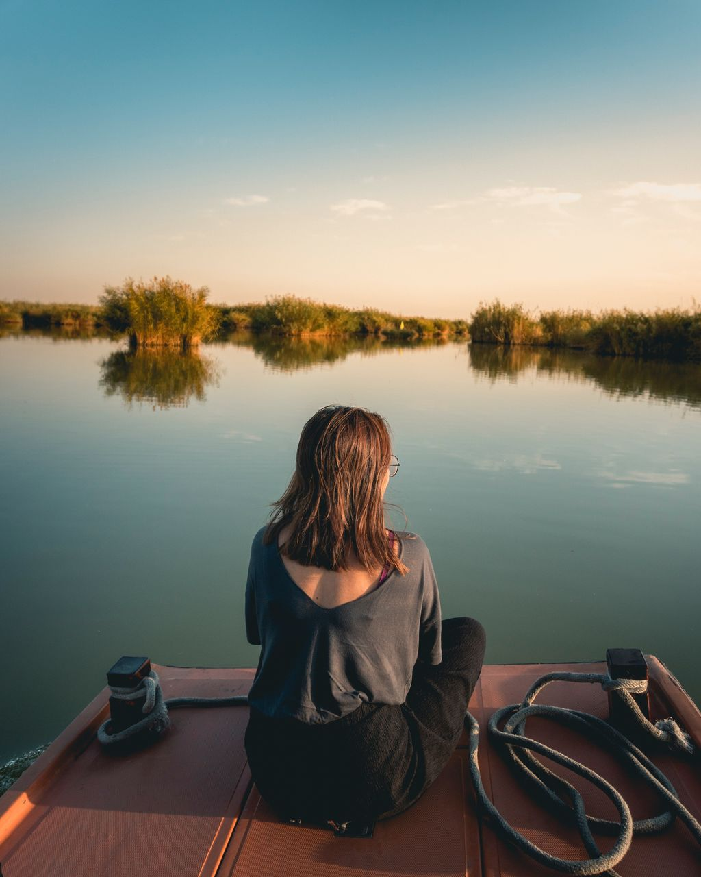 water, lake, one person, nature, real people, tranquility, rear view, tranquil scene, beauty in nature, sunset, sitting, reflection, scenics, outdoors, sky, tree, standing, day, nautical vessel, women, clear sky, people
