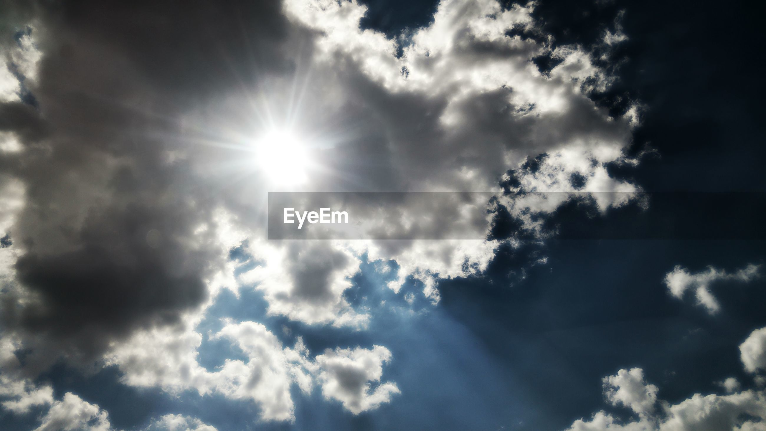 LOW ANGLE VIEW OF SUN SHINING OVER CLOUDS