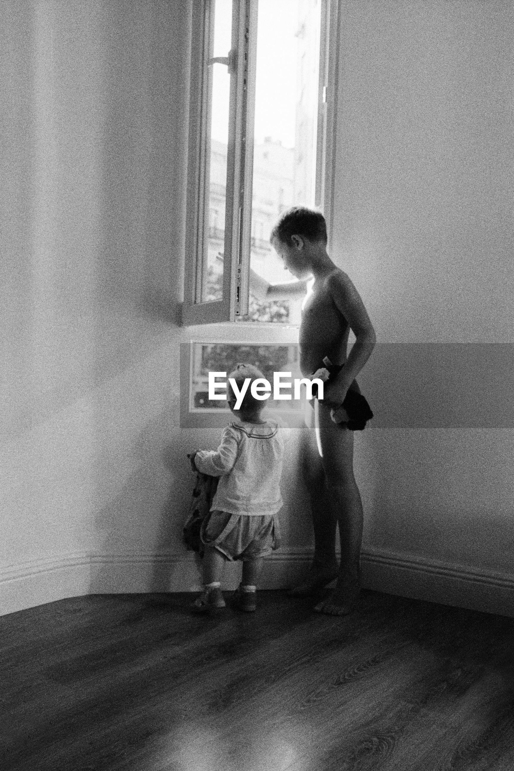 Full length of siblings looking through window while standing on hardwood floor at home