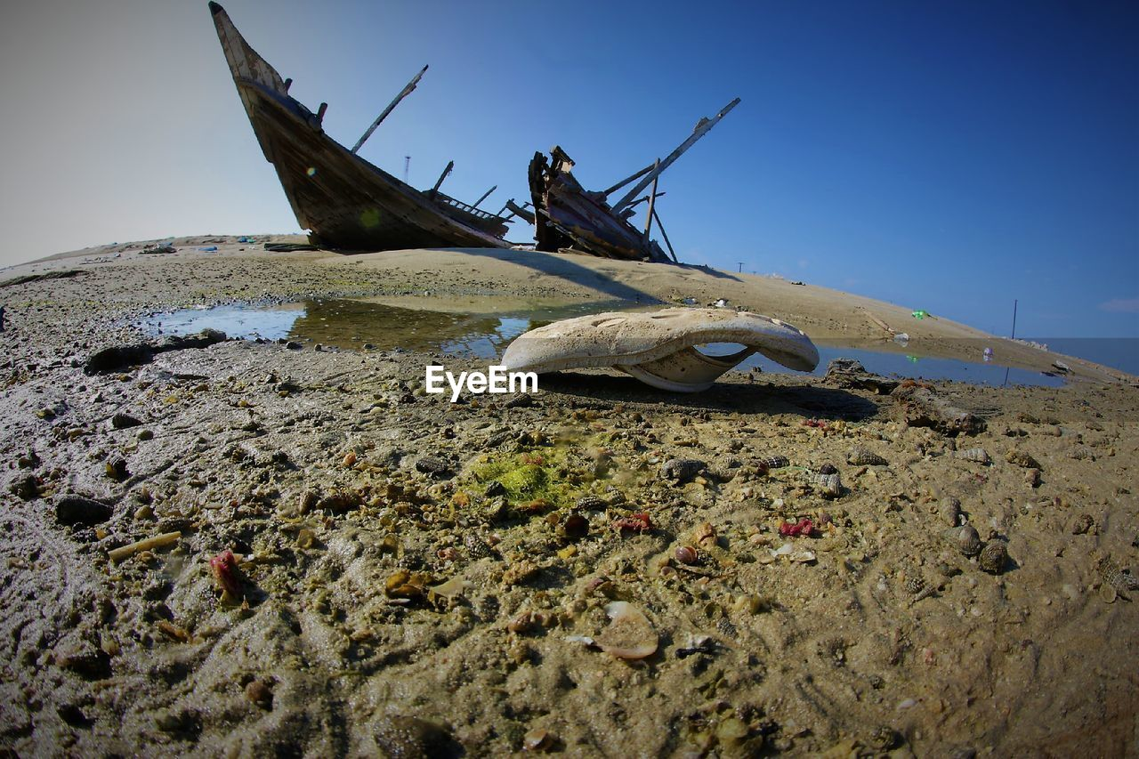 sky, land, nature, abandoned, day, mode of transportation, transportation, beach, nautical vessel, no people, sand, damaged, tranquility, obsolete, outdoors, shipwreck, old, metal, water, clear sky, deterioration