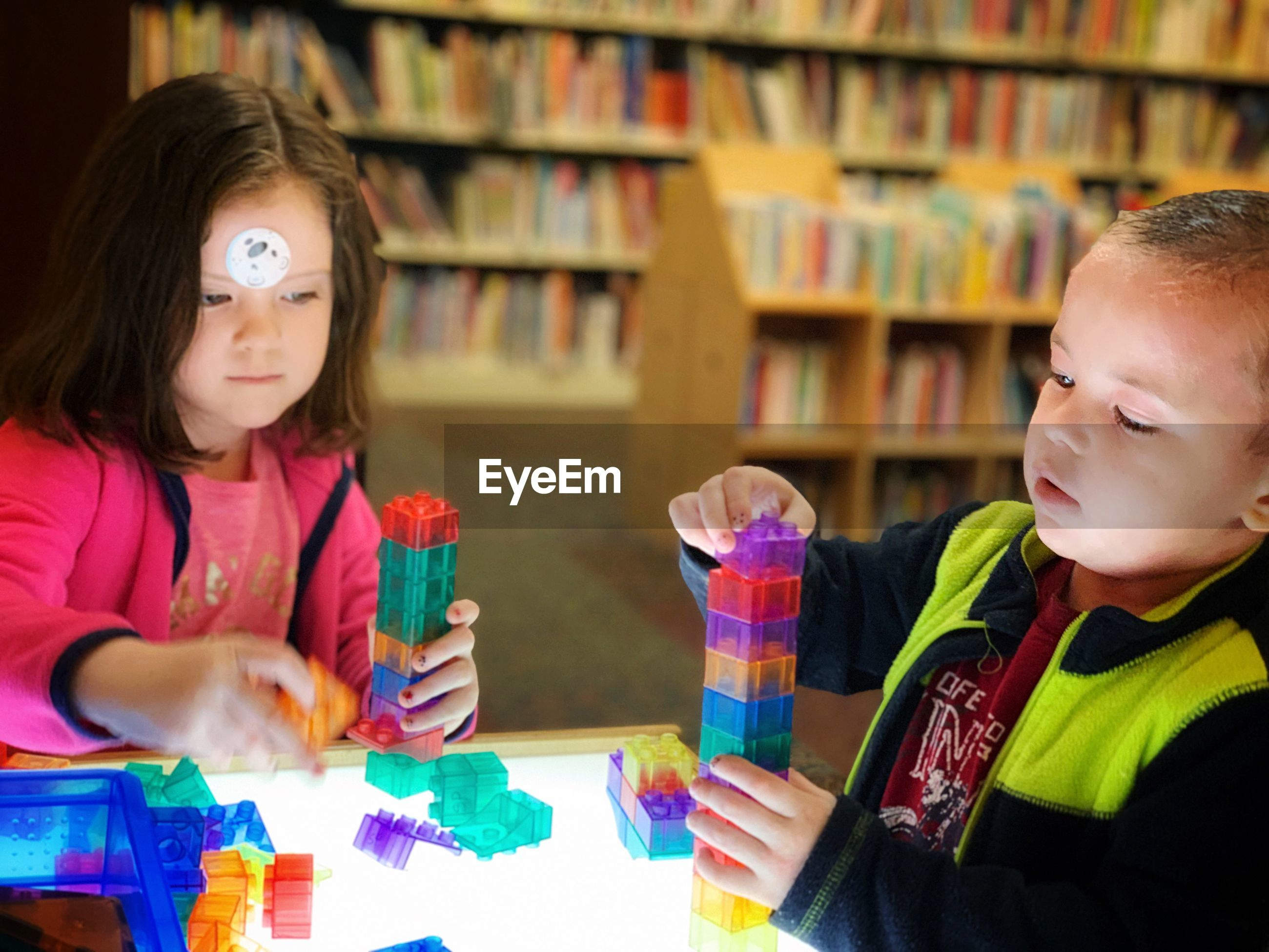 Siblings playing with toy blocks on table in library