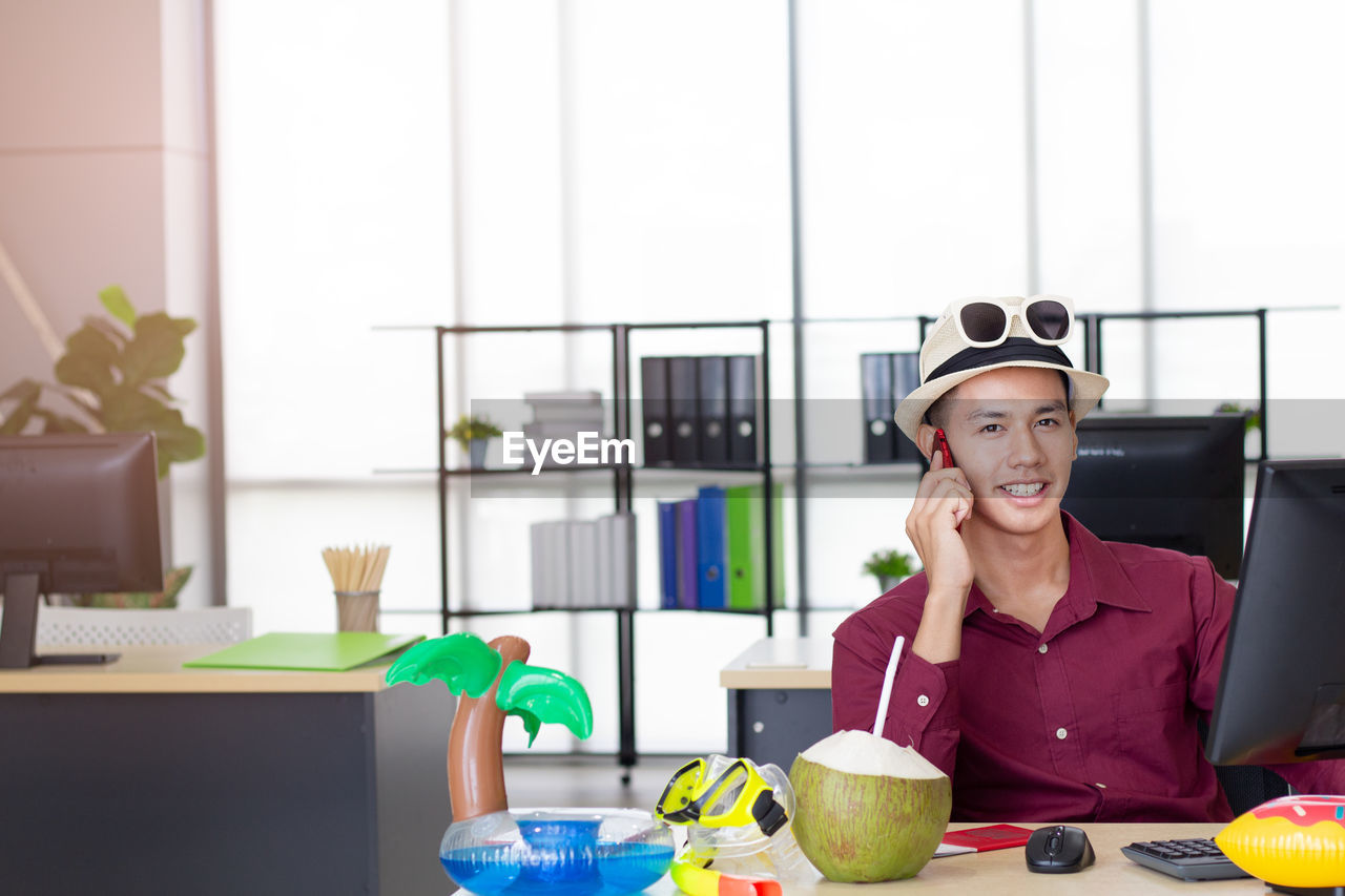 Portrait of smiling young man talking over smart phone while sitting at desk in office