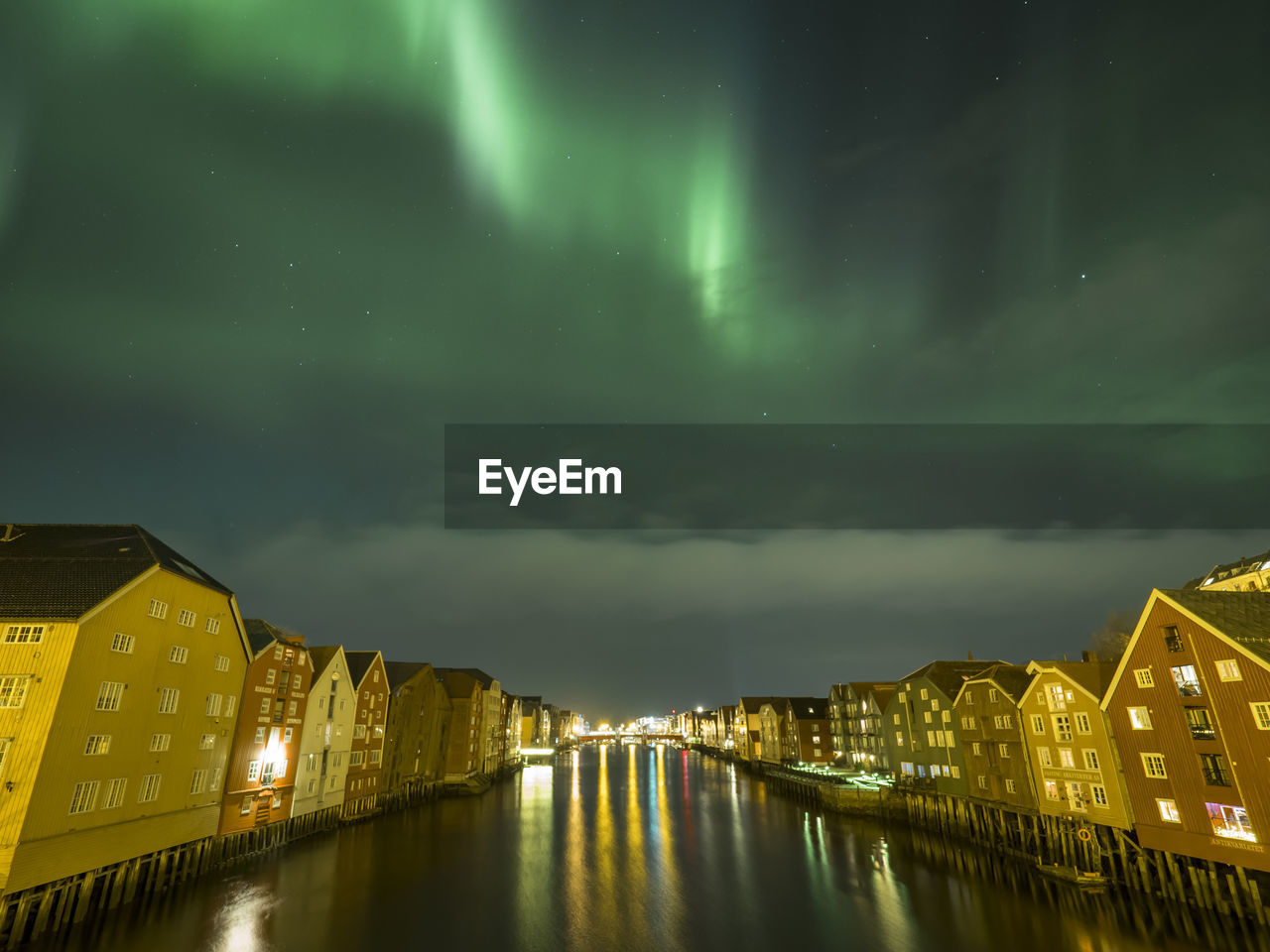 Canal In Illuminated City Against Aurora Borealis
