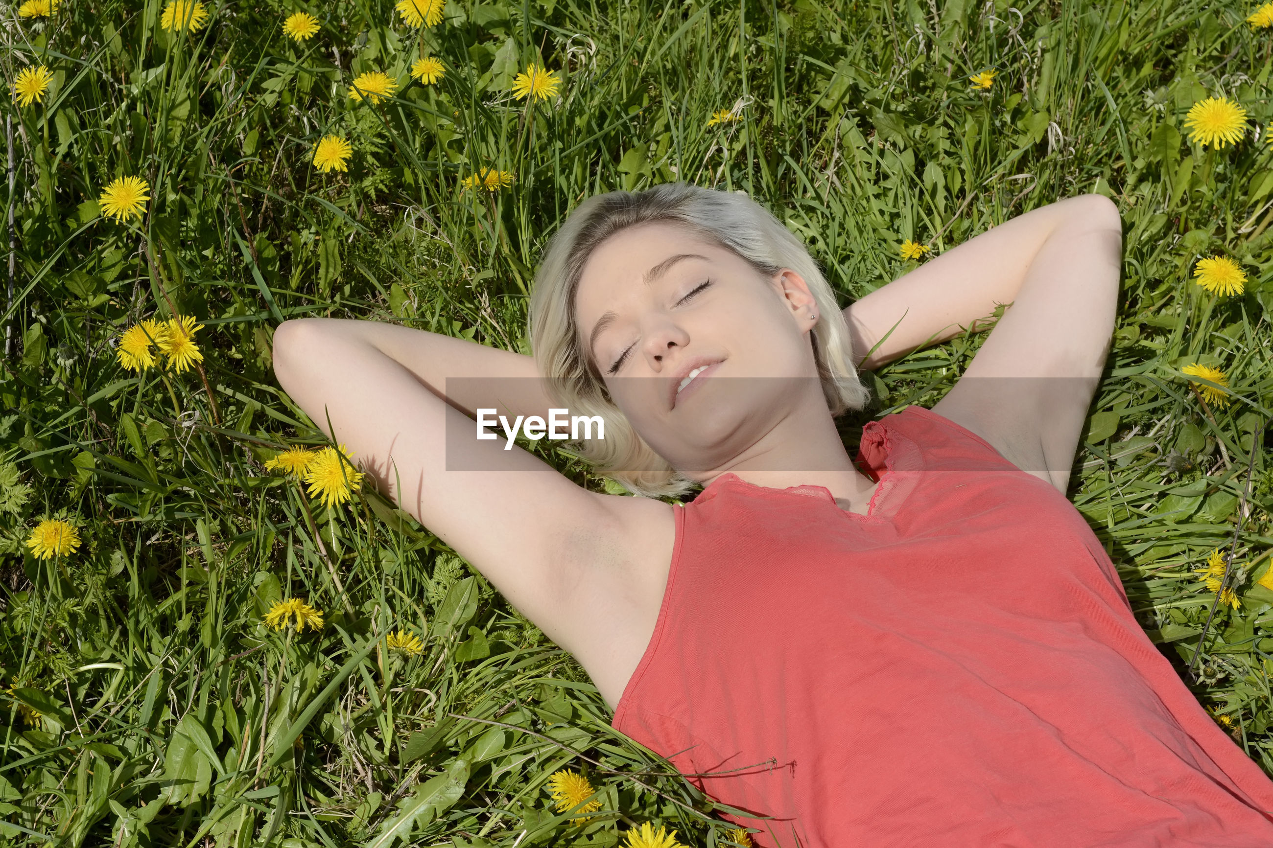 Young woman sleeping on grass