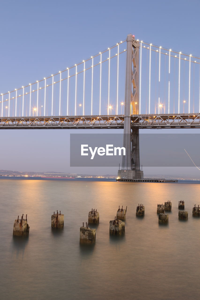 Low angle view of illuminated bay bridge over san francisco bay at dusk