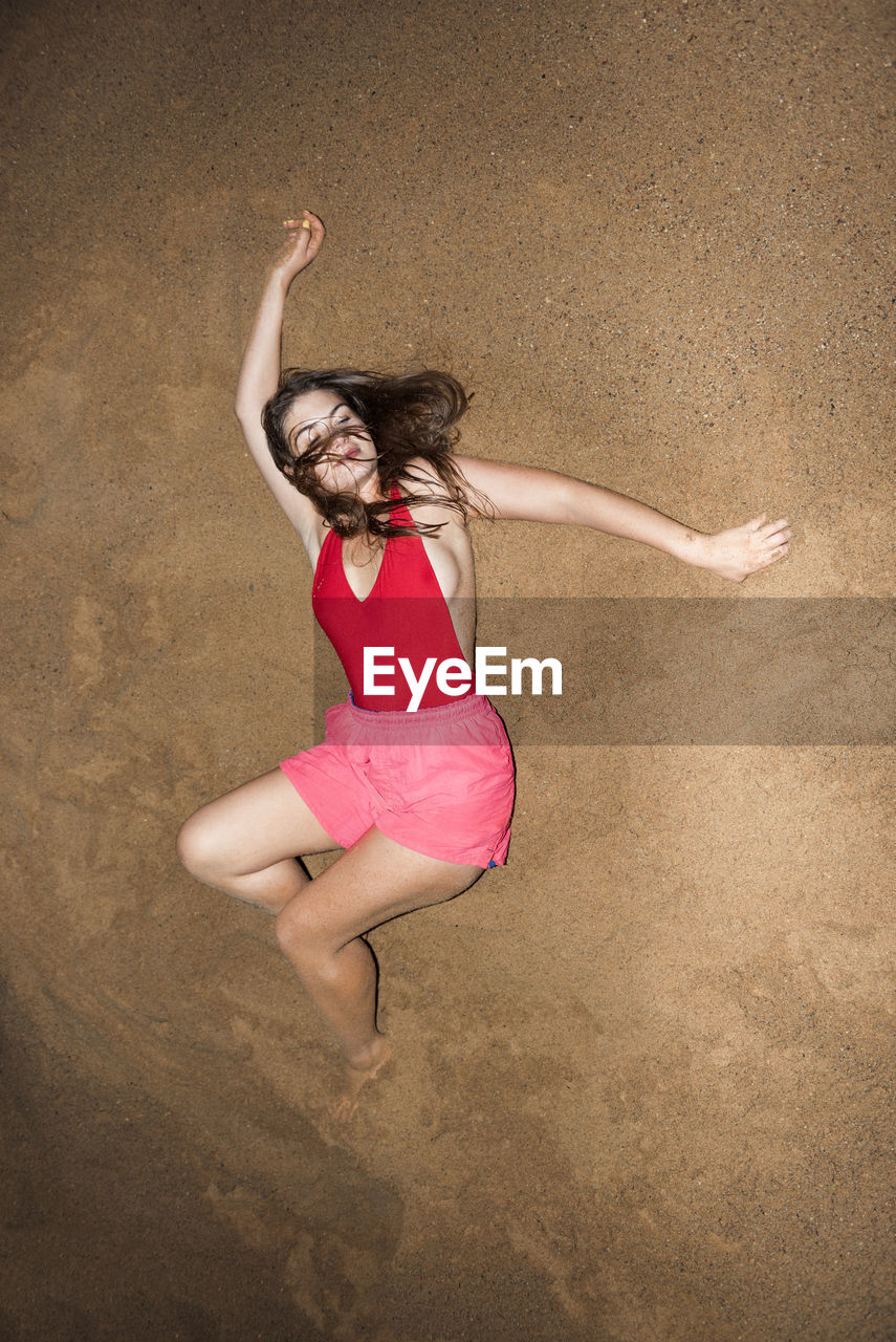High angle view of young woman lying at beach