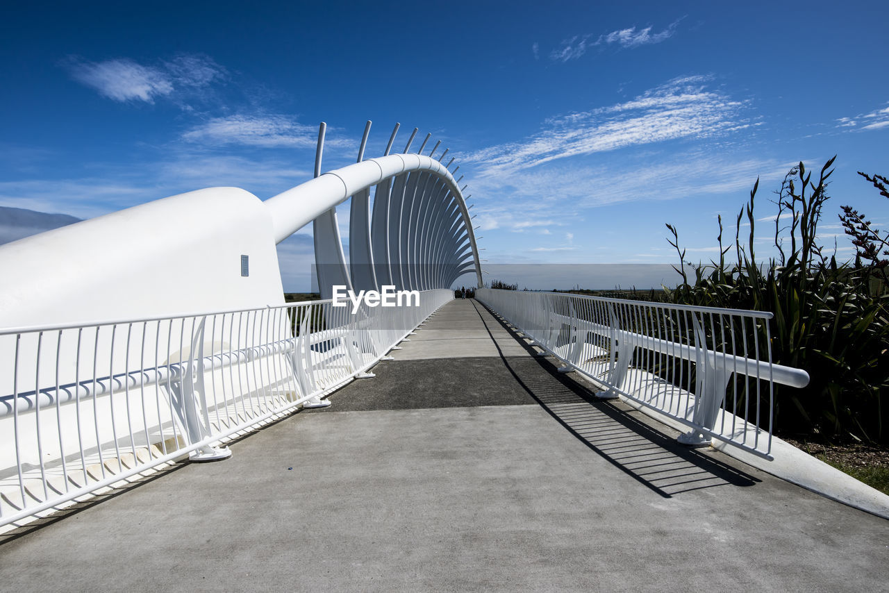 sky, cloud - sky, railing, nature, built structure, day, the way forward, architecture, sunlight, direction, diminishing perspective, outdoors, blue, no people, transportation, white color, connection, bridge, plant, environment, footbridge