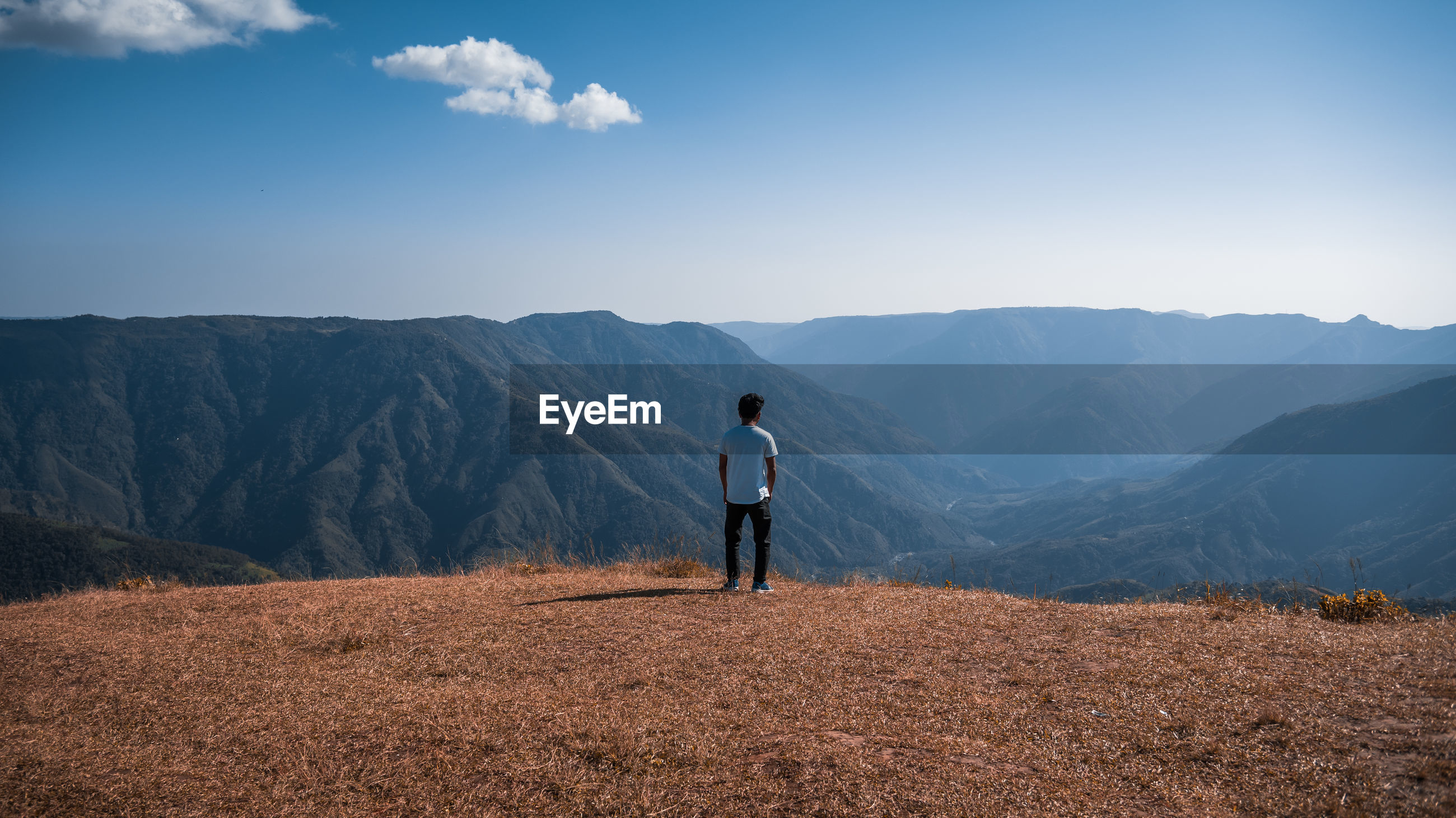 Rear view of man looking at view while standing against mountain range
