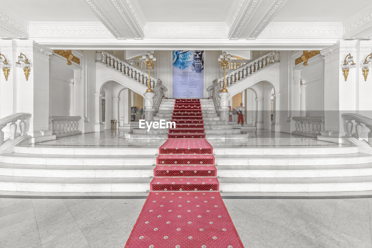 architecture, red, built structure, building, indoors, arch, flooring, architectural column, direction, white color, no people, the way forward, diminishing perspective, lighting equipment, ceiling, arcade, day, religion, celebration, tiled floor, luxury, ornate