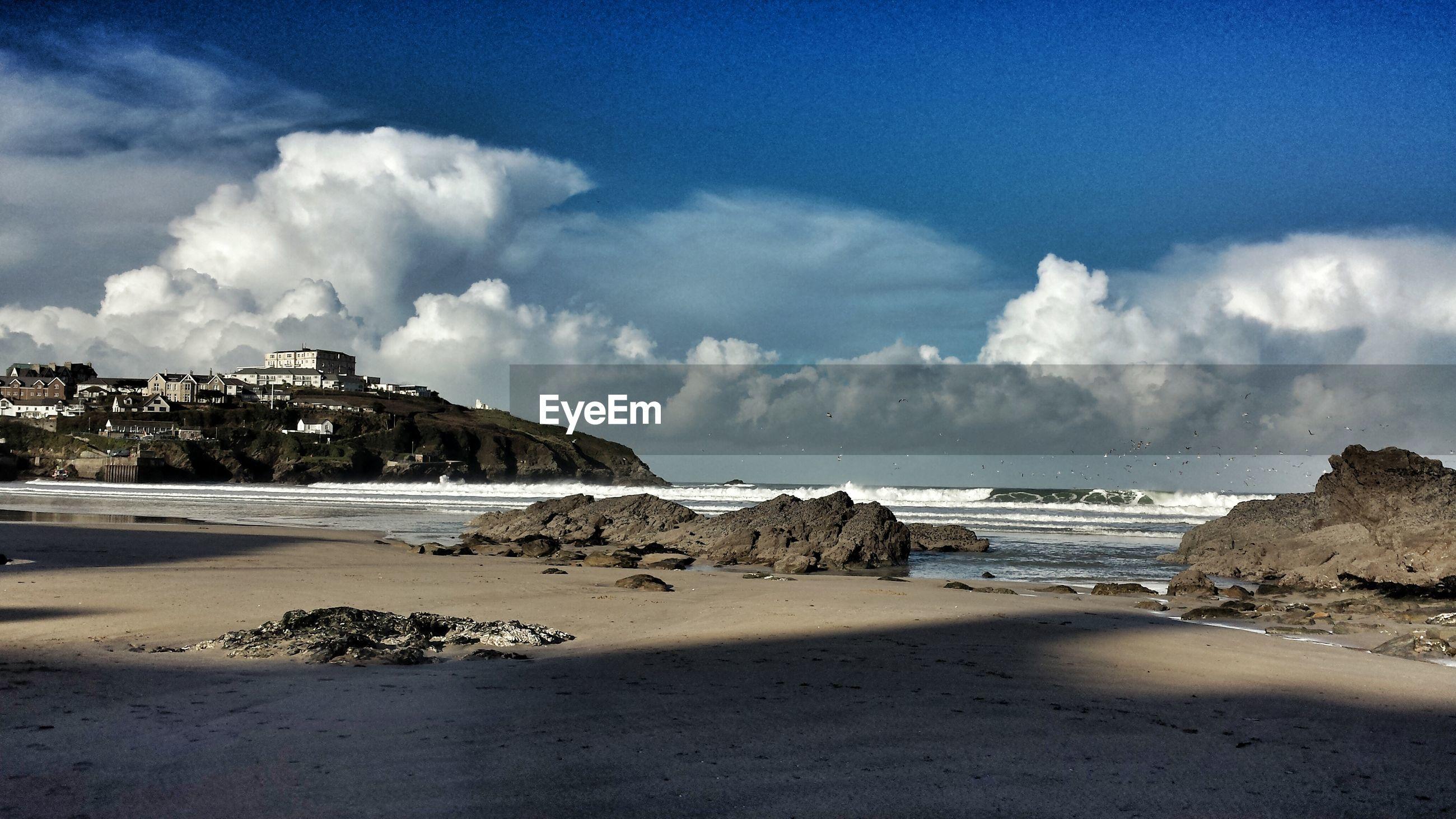 Scenic shot of calm beach against clouds