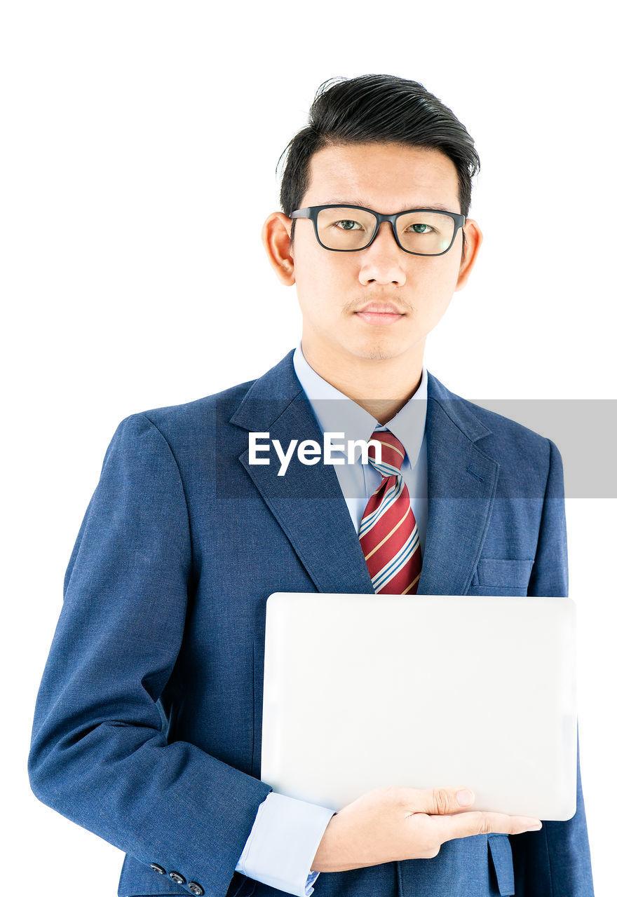 Portrait of businessman holding digital tablet standing against white background