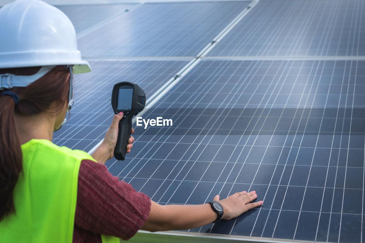 Rear view of woman examining solar panel