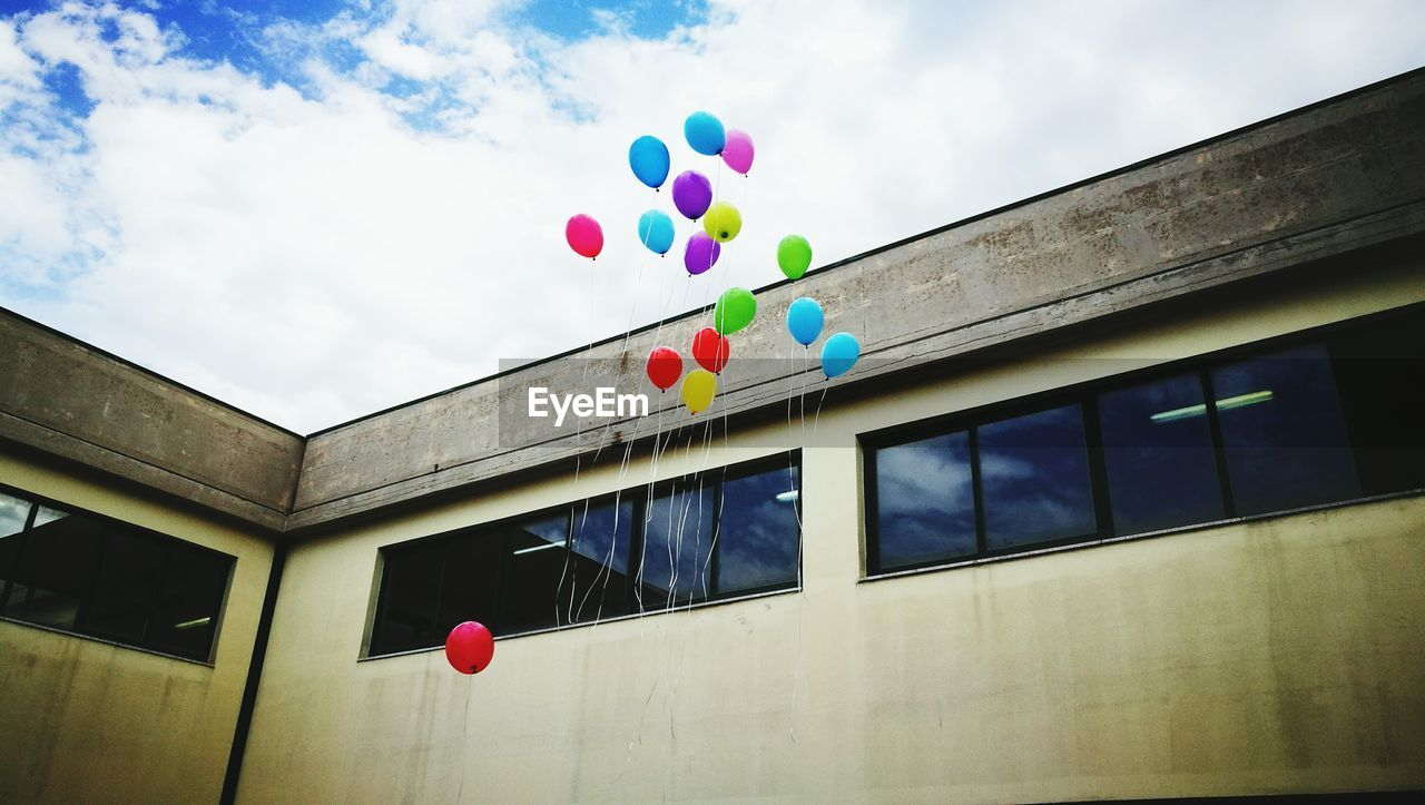 multi colored, balloon, built structure, low angle view, architecture, building exterior, helium balloon, no people, sky, day, celebration, nature, decoration, cloud - sky, event, hanging, outdoors, building, mid-air, wall - building feature